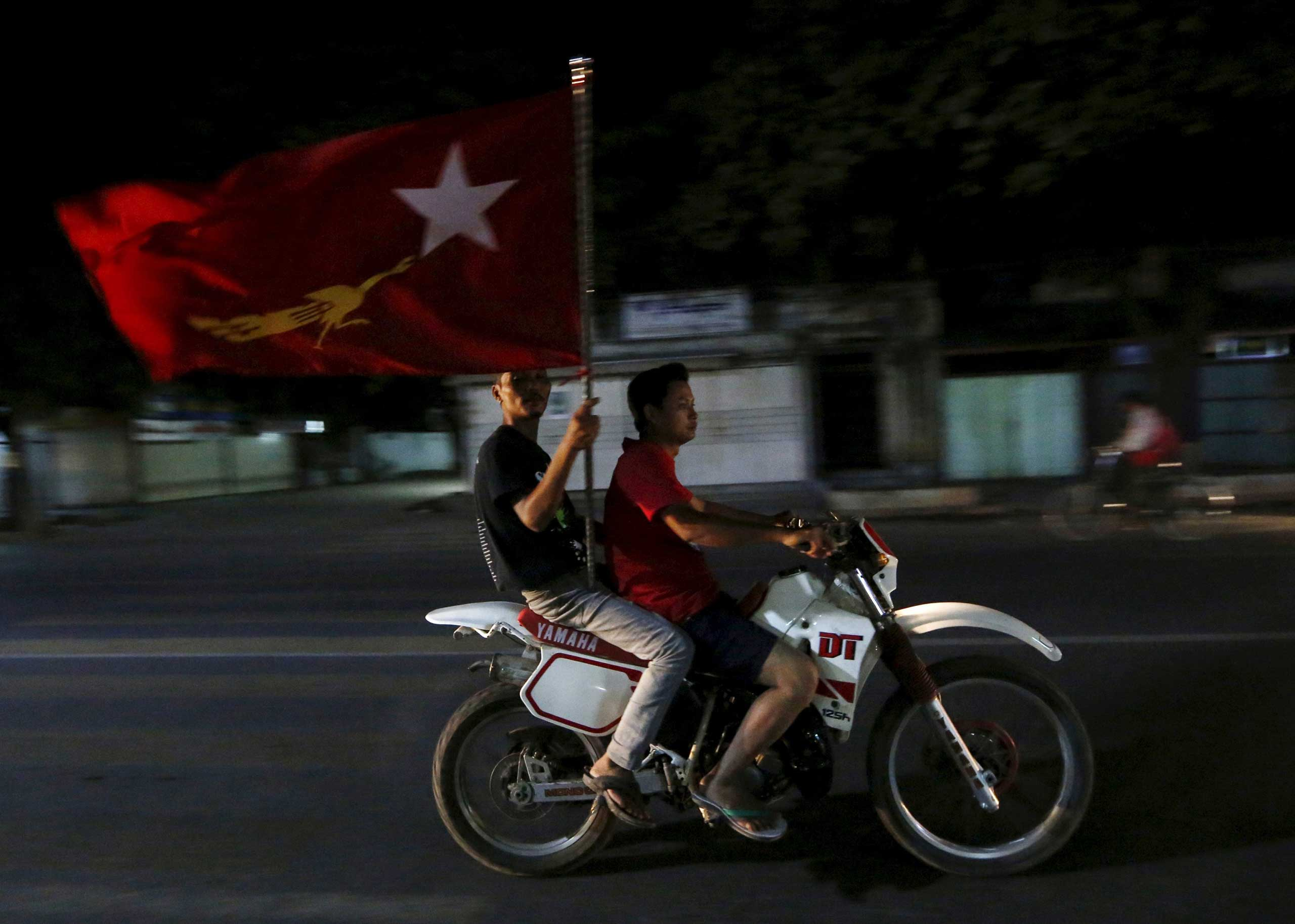 Supporters of Aung San Suu Kyi carry a National League for Democracy (NLD) flag through the streets of Mandalay, Burma, on Nov. 9, 2015.