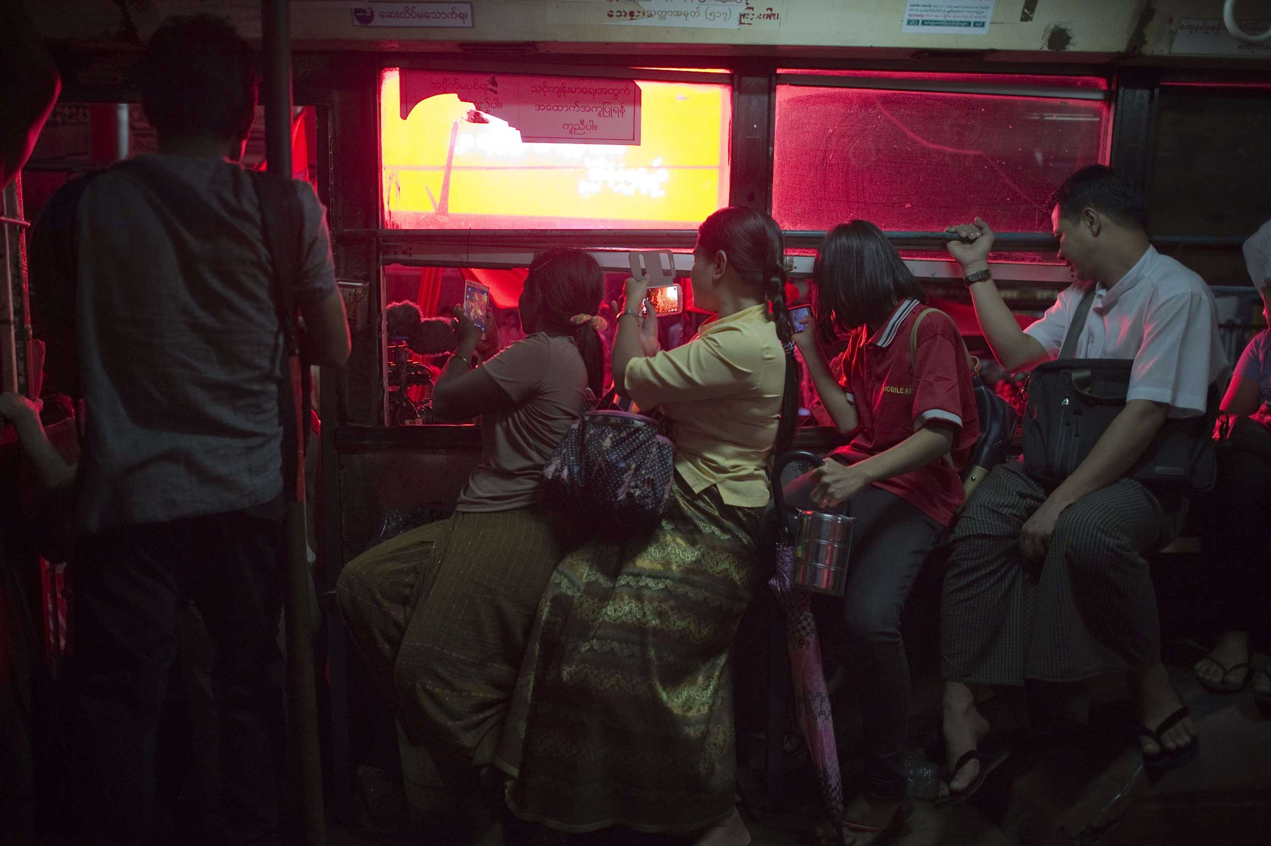 People riding a bus look at supporters of Aung San Suu Kyi as they celebrate outside the National League of Democracy (NLD) headquarters in Rangoon, Burma, on Nov. 9, 2015.