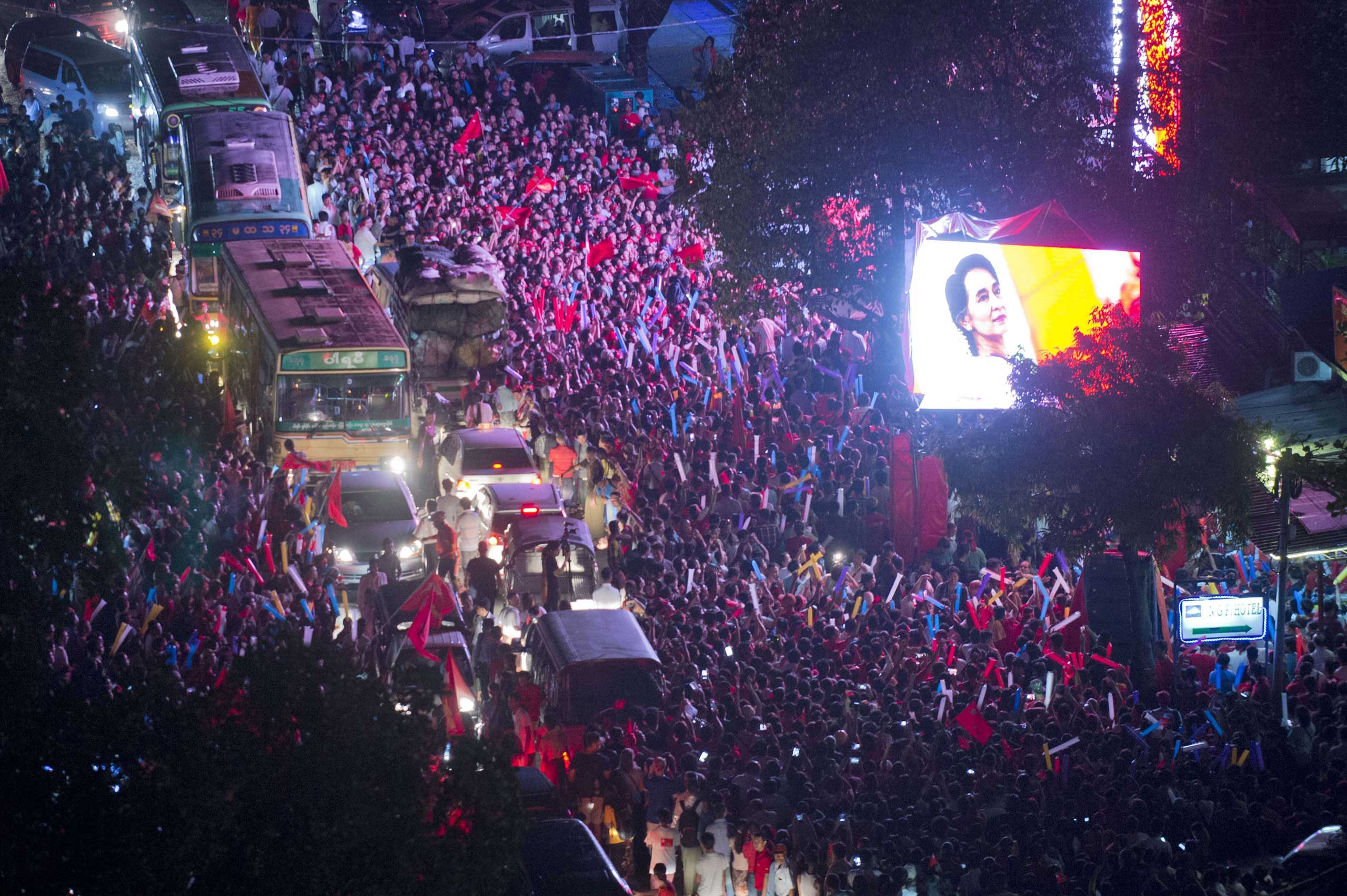 A huge crowd gathers outside the headquarters of National League of Democracy (NLD) party displaying a huge portrait of Aung San Suu Kyi in Rangoon, Burma, on Nov. 9, 2015.