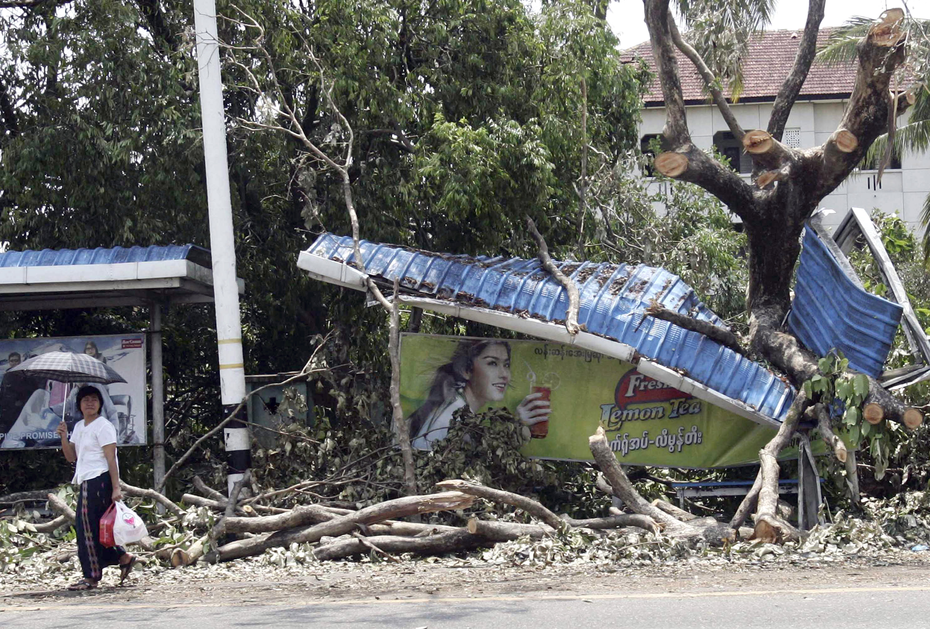 A Myanmar girl makes her way past a bus station destroyed by the cyclone that hit Yangon on May 6, 2008.