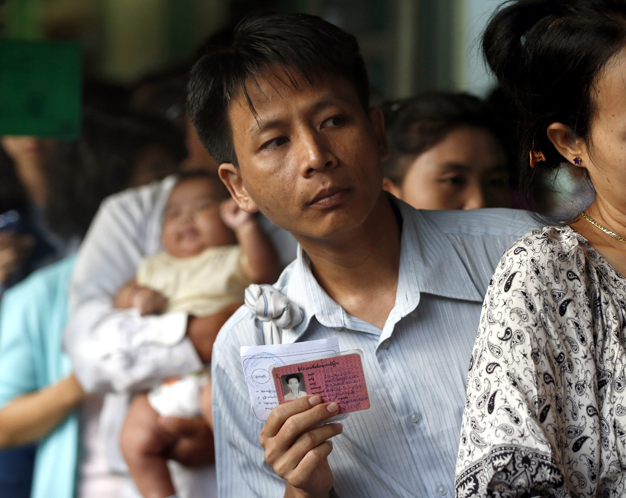 A voter holds his citizen ID card while lining up to cast his ballot at a polling station in Yangon, Burma on Nov. 8, 2015.