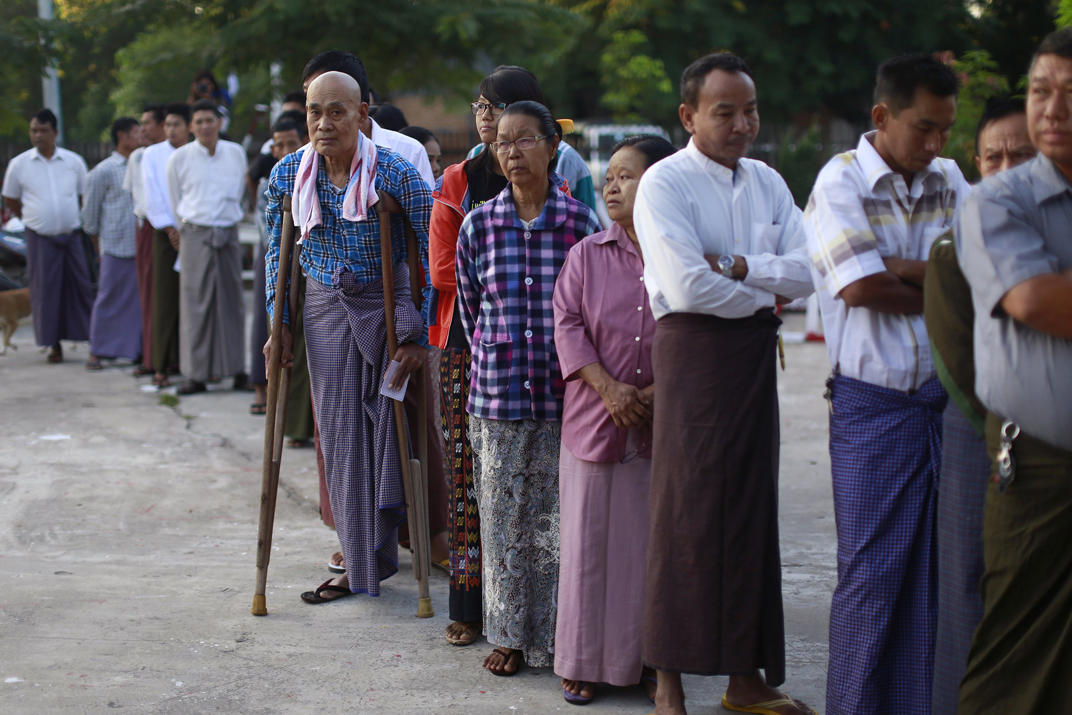 People stand outside a polling station in Mandalay, Burma on Nov. 8, 2015.