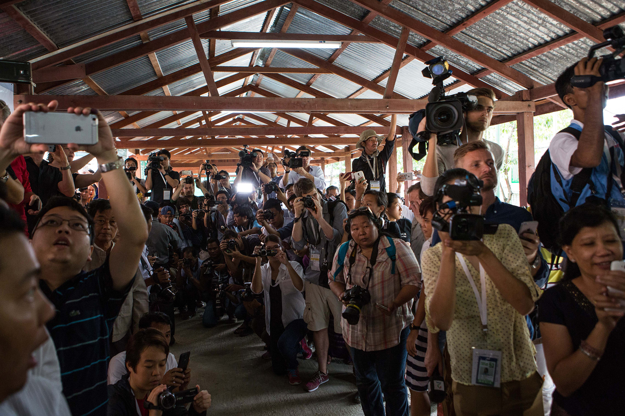 The media prepares as Aung San Suu Kyi, leader of Burma's National League for Democracy party, arrives at a polling station in Yangon, on Nov. 8, 2015.
