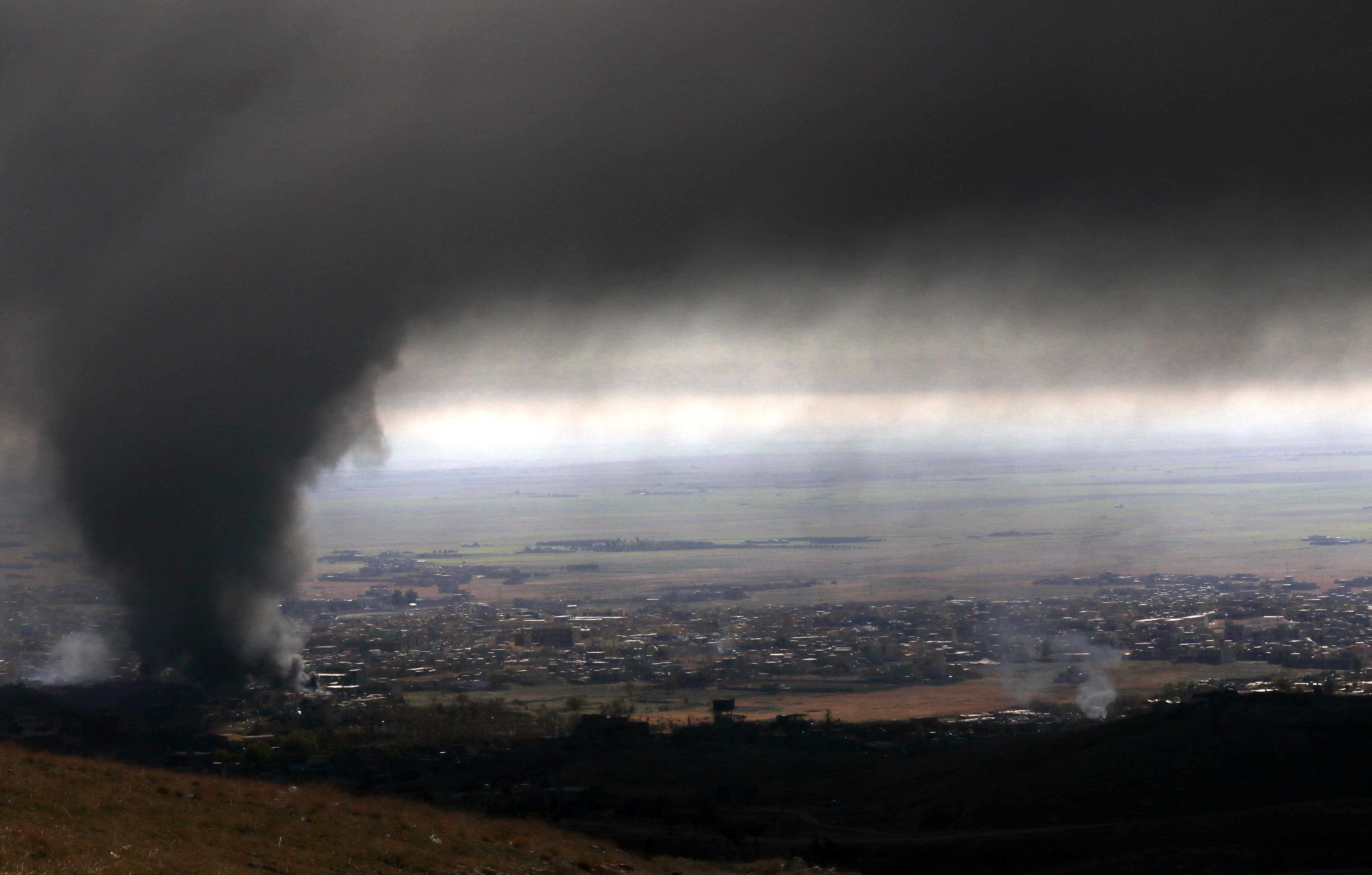 Heavy smoke covers the northern Iraqi town of Sinjar during an operation by Iraqi Kurdish forces backed by US-led strikes, on Nov. 12, 2015.