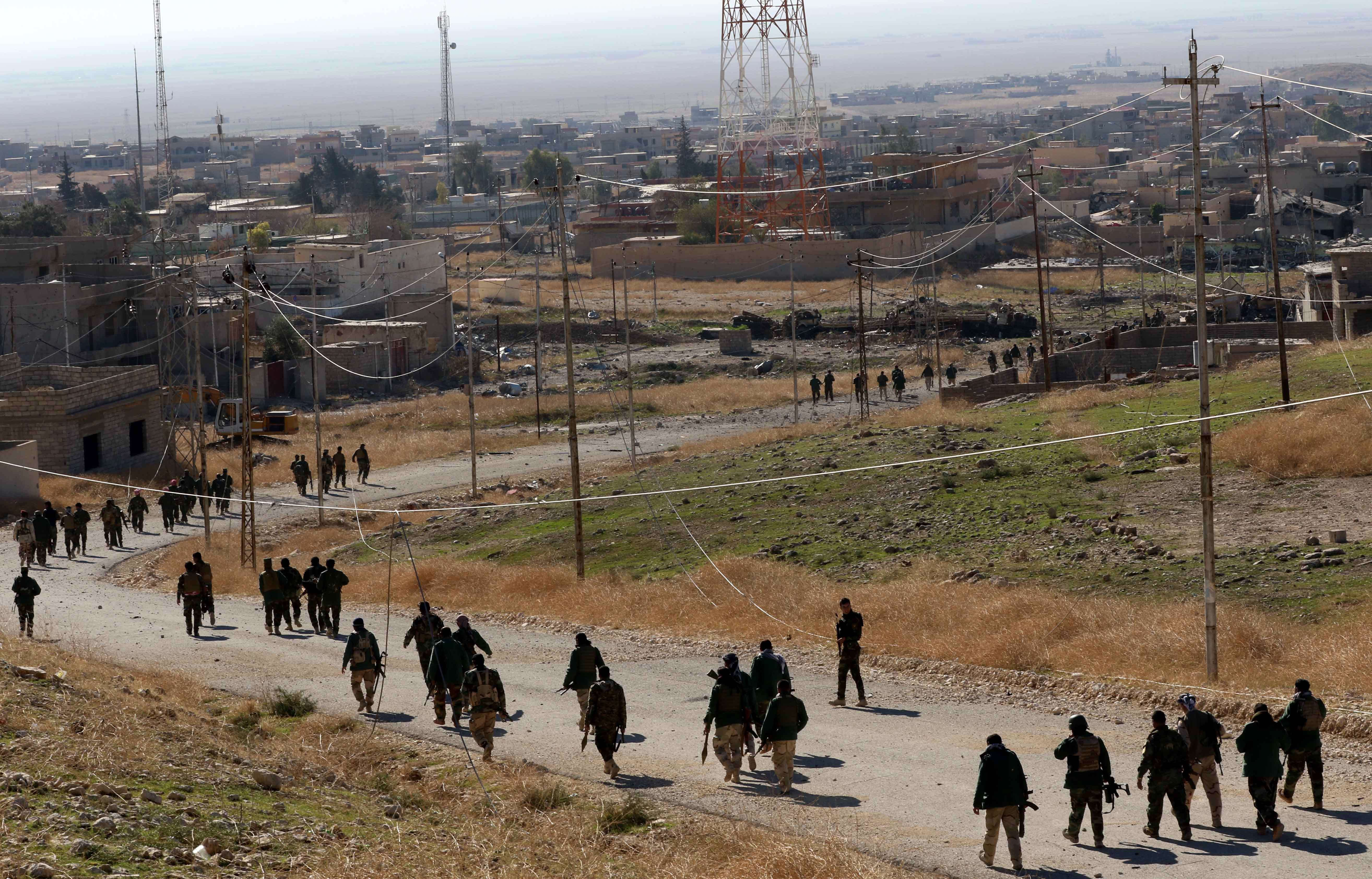 Iraqi Kurdish forces and fighters from the Yazidi minority, a local Kurdish-speaking community targeted in a brutal ISIS campaign of massacres, enslavement and rape, enter the Iraqi city of Sinjar on Nov. 11, 2015.