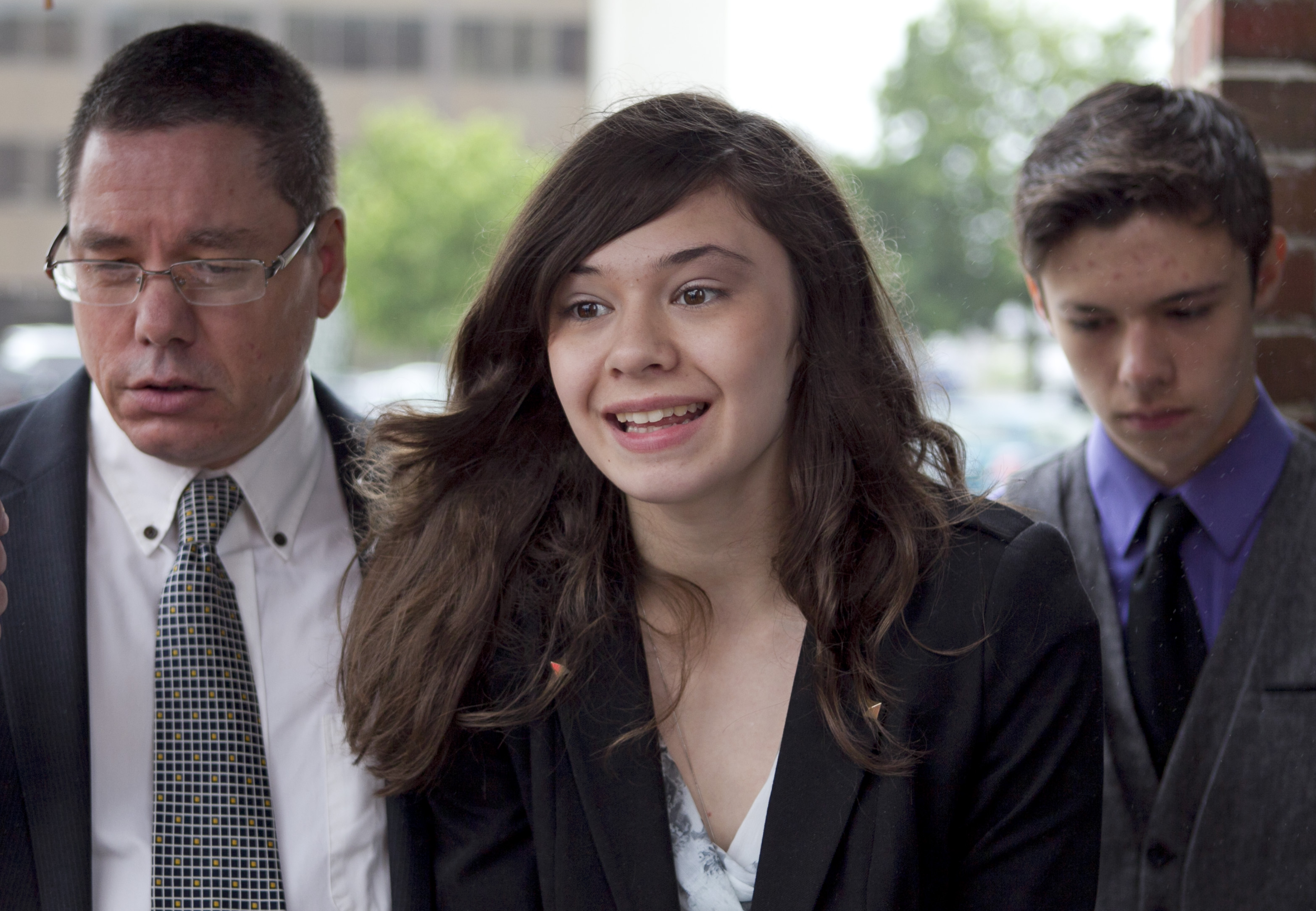Transgender student Nicole Maines, center, speaks to reporters as her father Wayne Maines, left, and brother Jonas, look on outside the Penobscot Judicial Center in Bangor, Maine, on June 12, 2013.