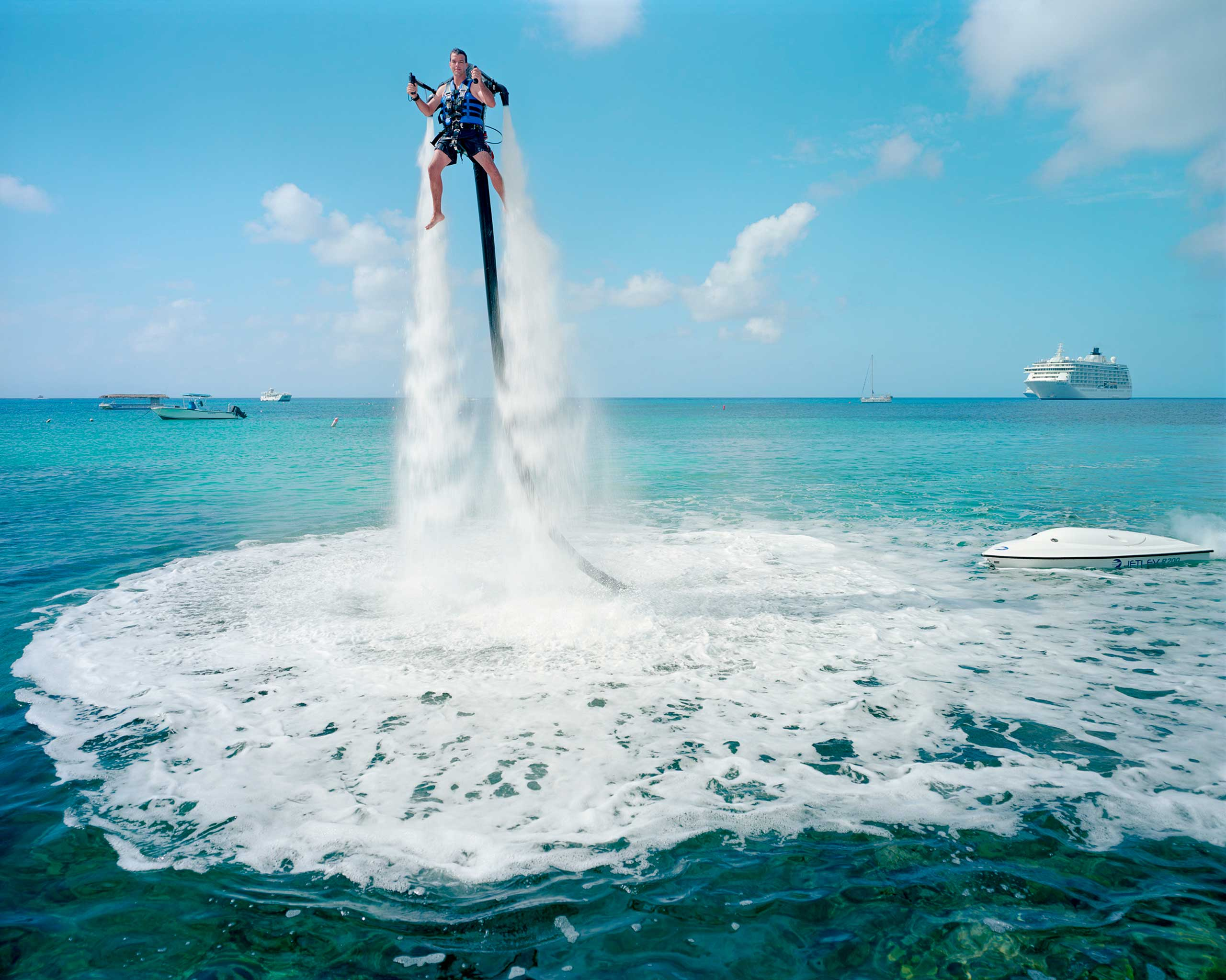 "An employee of ""Jetpack Cayman"" demonstrates this new watersport, now available on the island. A 2000cc motor pumps water up through the Jetpack, propelling the client out of the sea ($359 for a 30-minute session). Mike Thalasinos, the owner of the company, remarks, ""The Jetpack is zero gravity, the Cayman are zero taxes, we are in the right place!"" Grand Cayman."