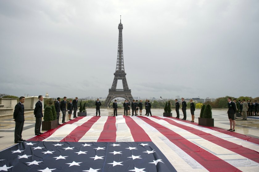 Student officers display an American flag on the Trocadero square with the Eiffel tower in the background during a solemn tribute to the victims of the 9/11 attacks on Sept. 11, 2011 in Paris.