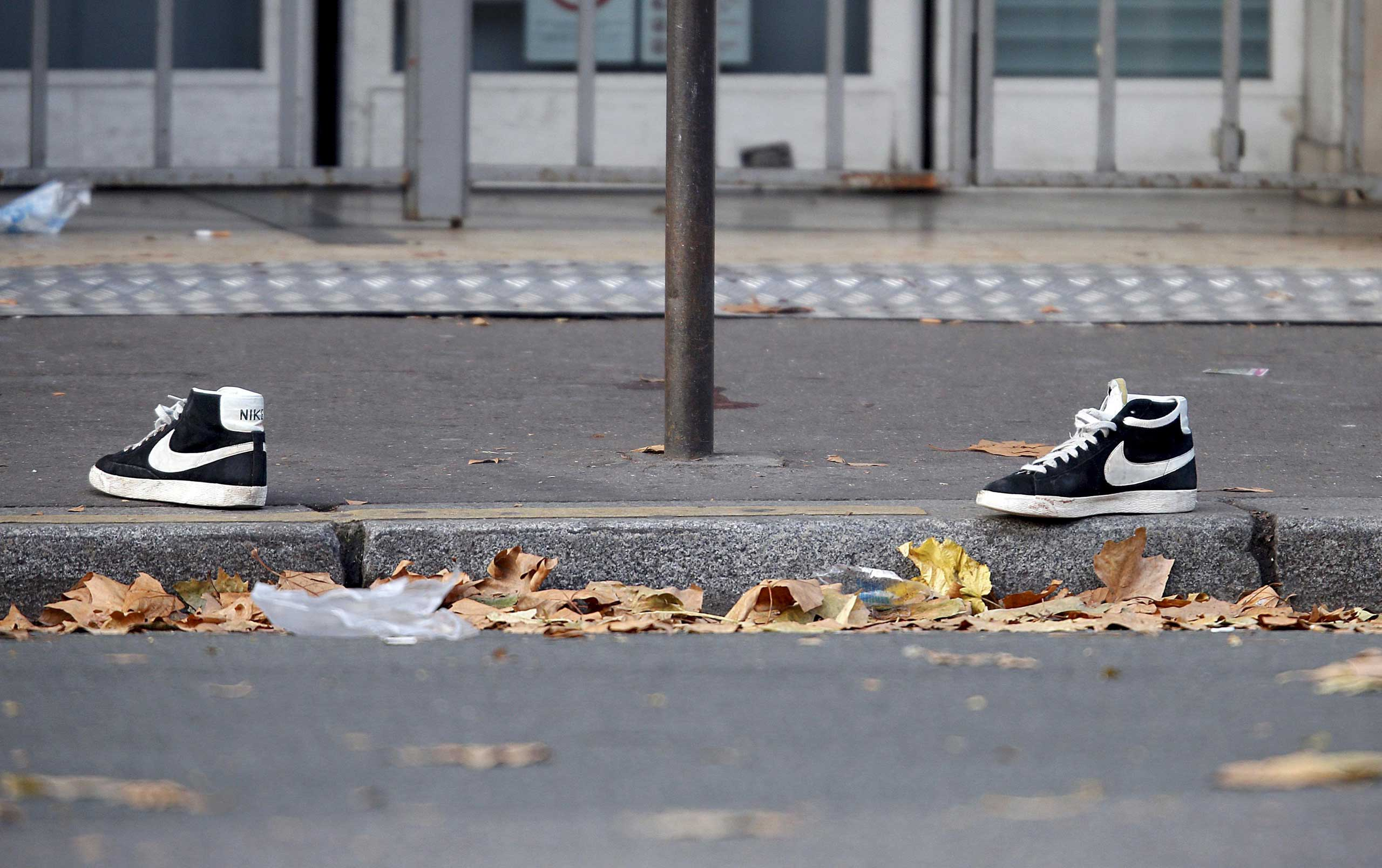 A pair of abandoned shoes seen left in the street near the Bataclan concert hall the morning after a series of deadly attacks in Paris, Nov. 14, 2015.