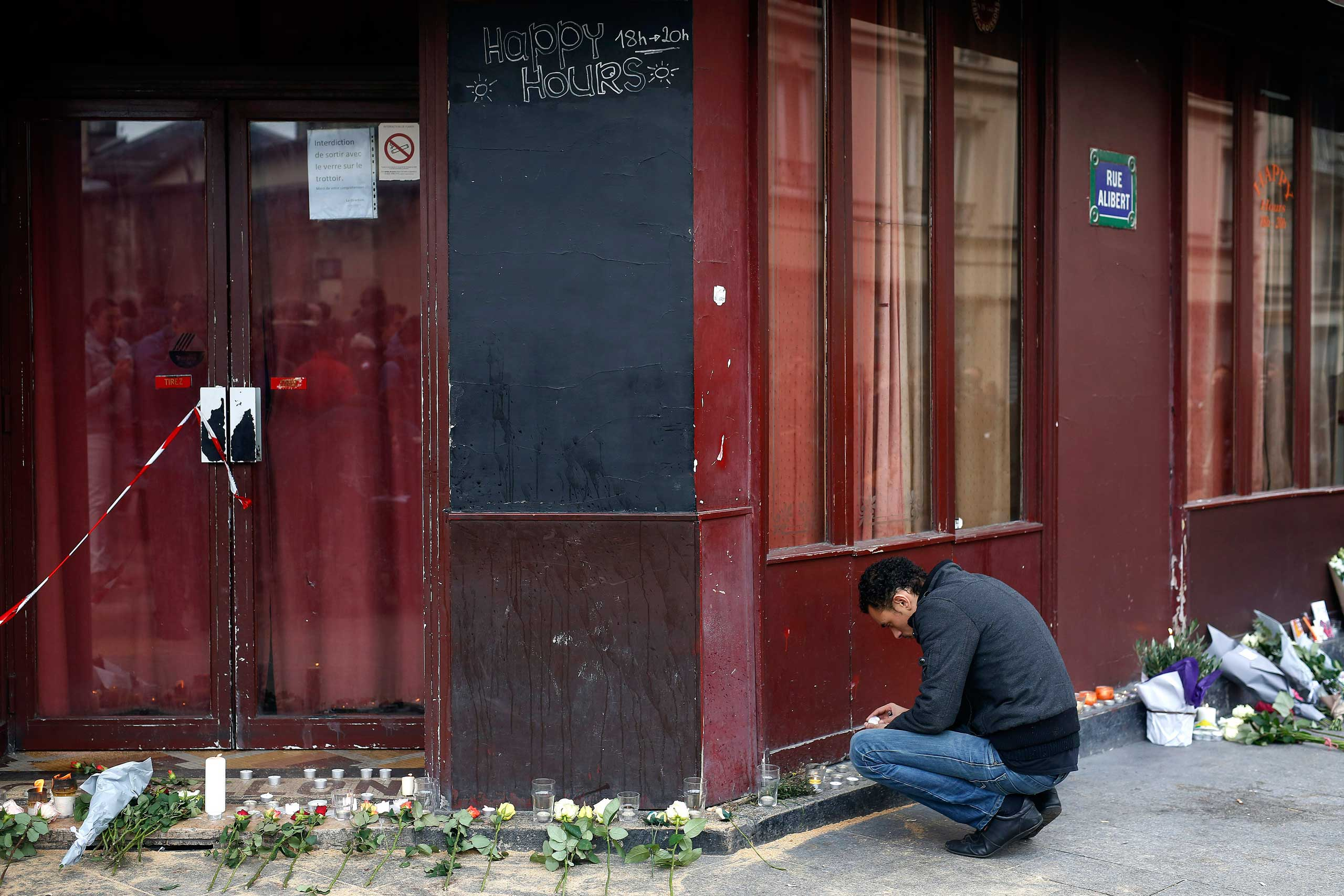 A man places a candle in front of the Carillon cafe in Paris, on Nov. 14, 2015.