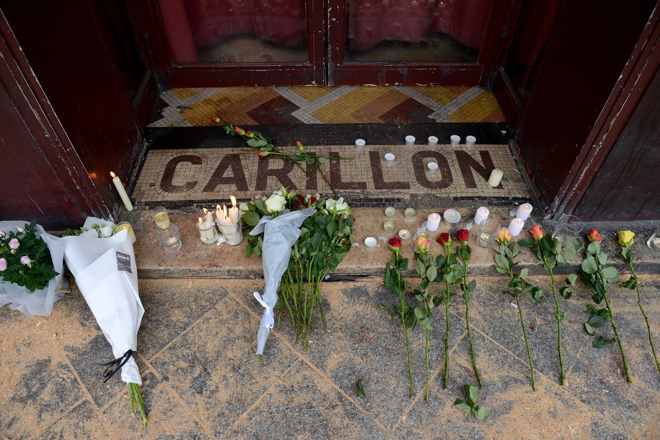 Flowers and candles are placed in tribute outside Le Carillon bar, in Paris, on Nov. 14, 2015.