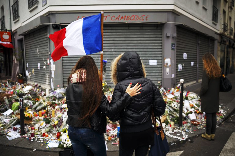 Two women stand outside the Petit Cambodge restaurant Tuesday, Nov. 17, 2015, at a site of last Friday's attacks in Paris.