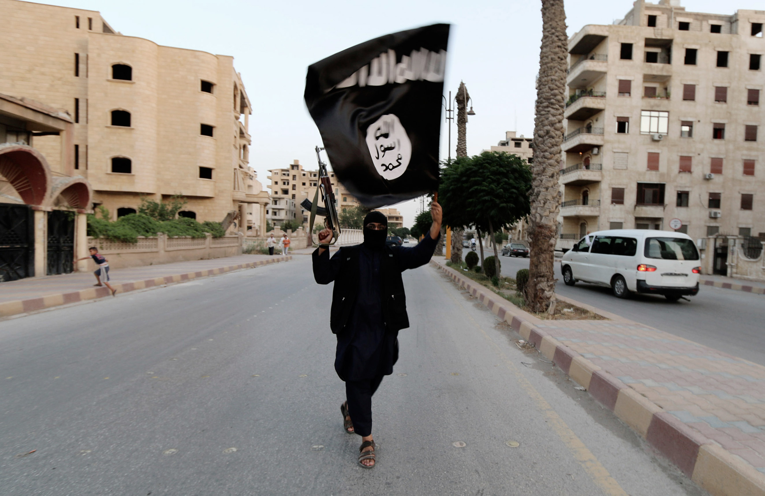 A member loyal to the Islamic State in Iraq and the Levant (ISIL) waves an ISIL flag in Raqqa on June 29, 2014.