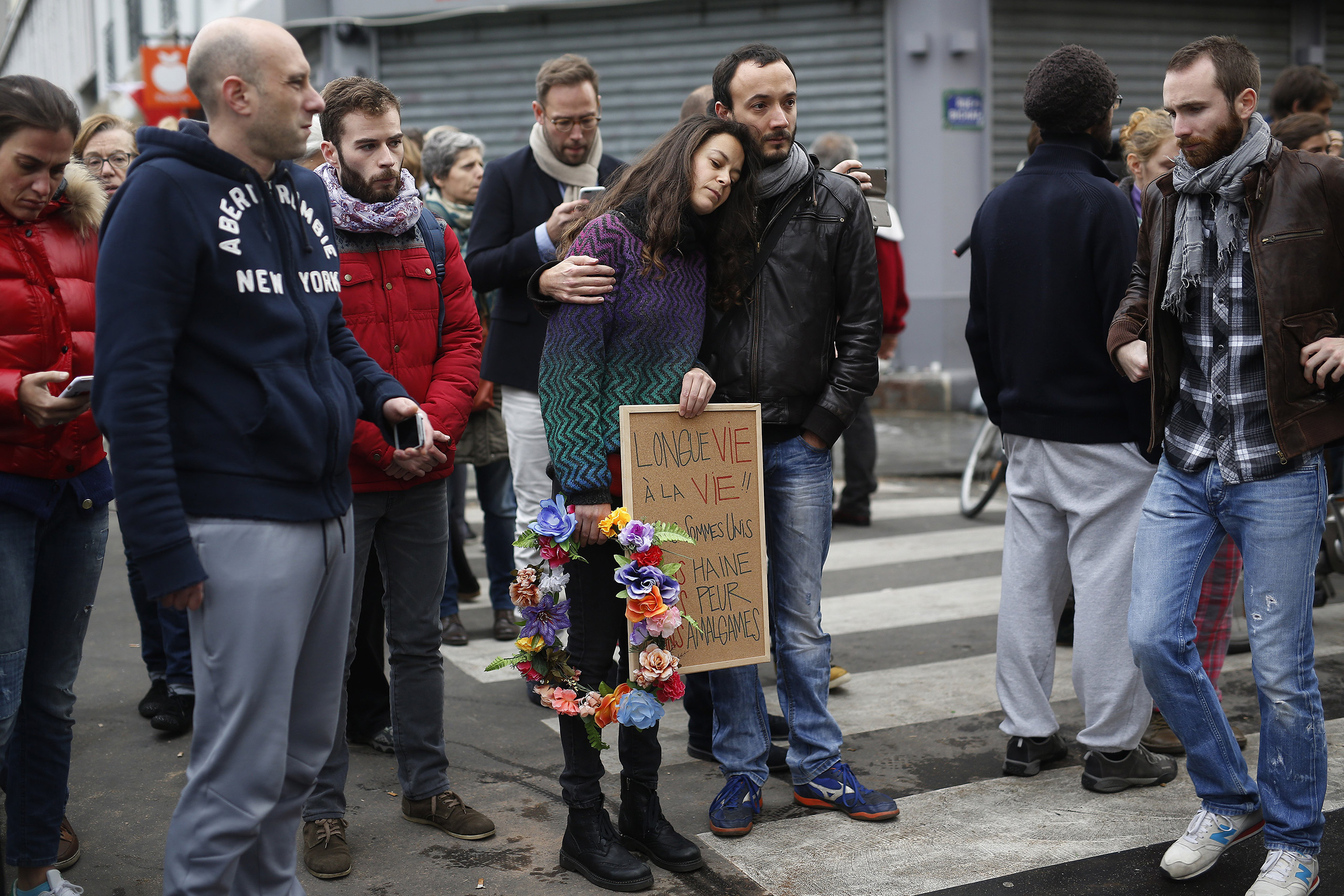 People react in front of  the Carillon cafe and the Petit Cambodge restaurant  in Paris Saturday Nov. 14, 2015.