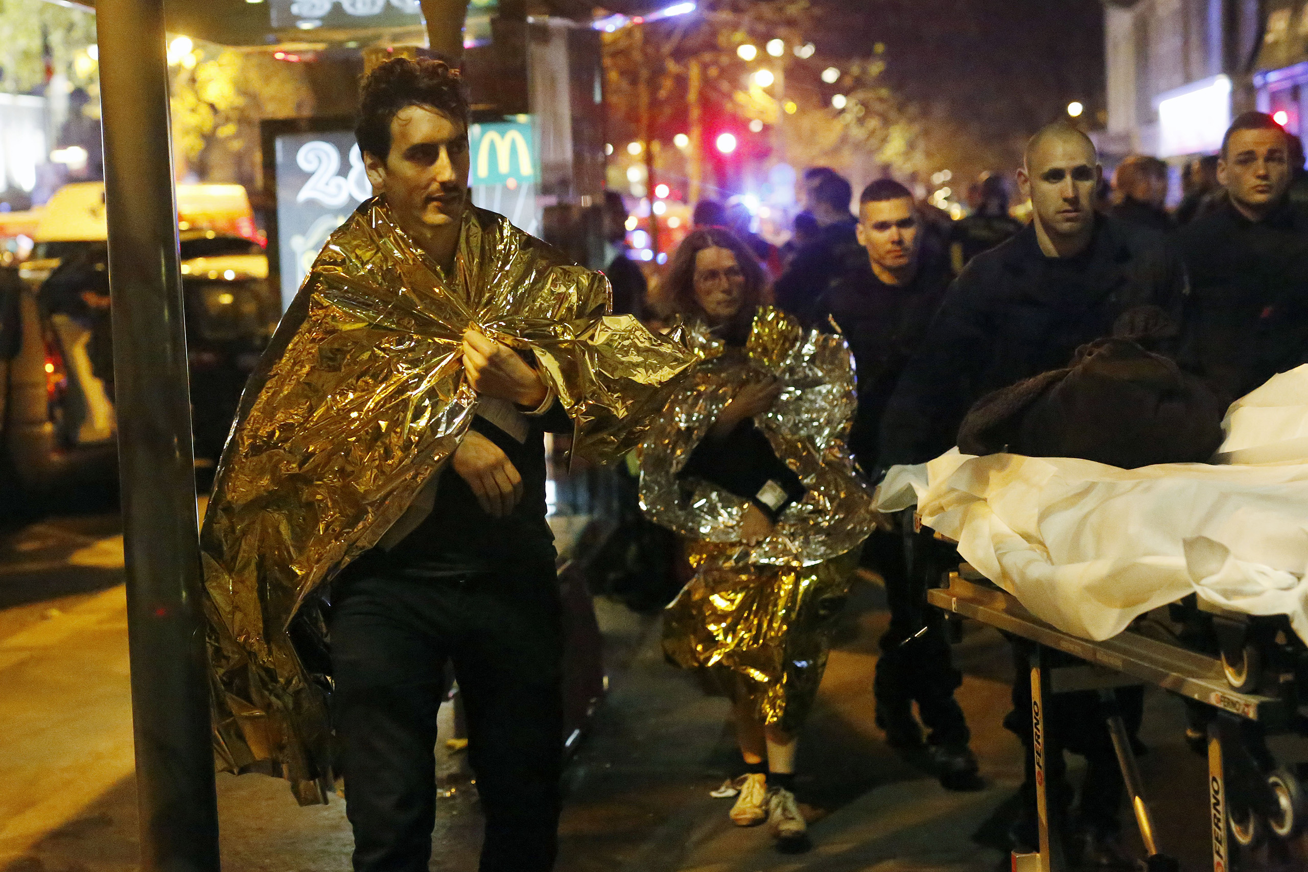 Victims walk away outside the Bataclan theater in Paris on Nov. 13, 2015.