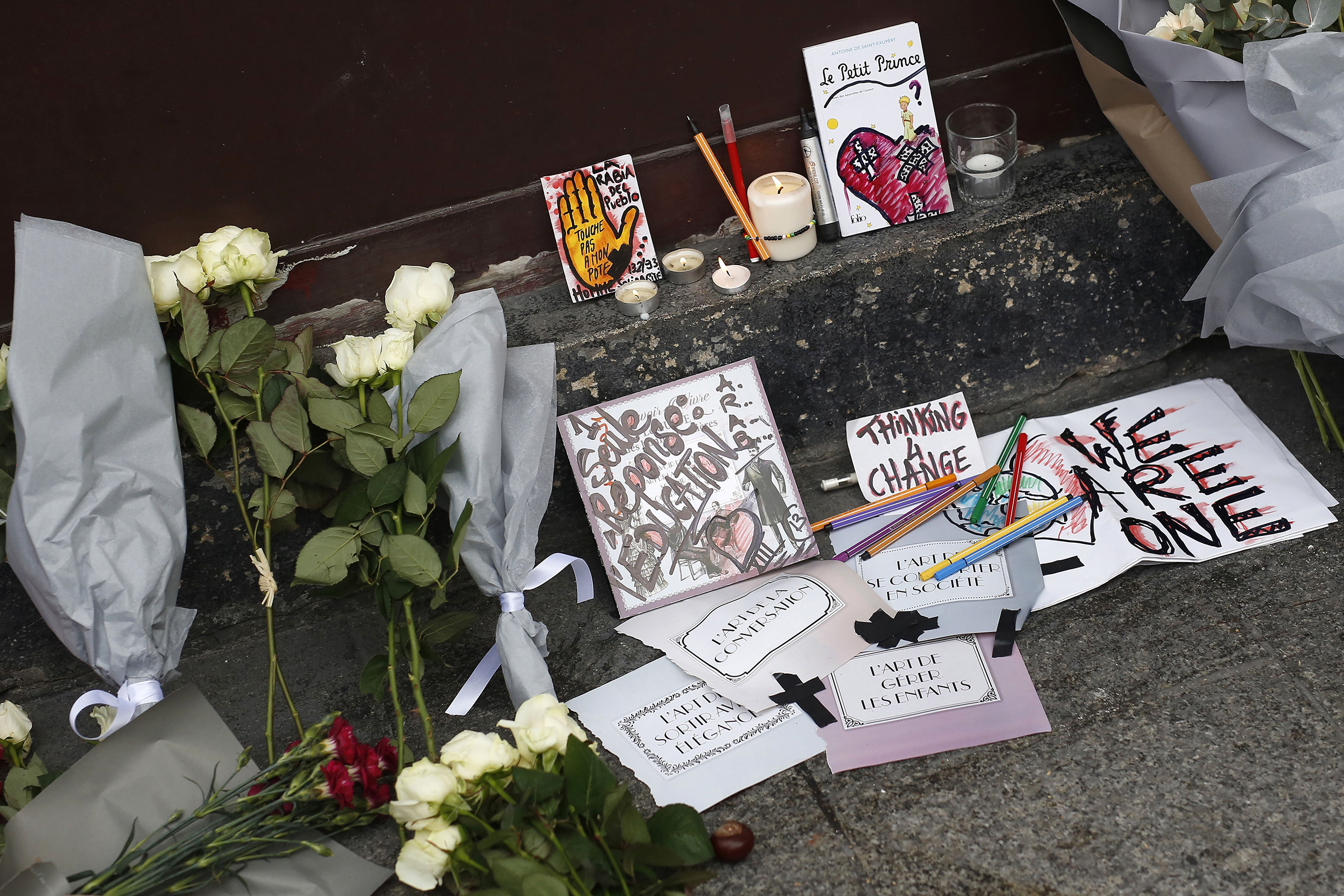 Cards, candles and flowers are placed in front of the Carillon cafe in Paris on Saturday Nov. 14, 2015.