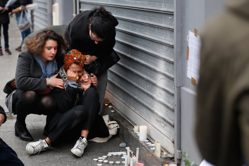 A woman is comforted by others outside the Carillon cafe and the Petit Cambodge restaurant in Paris on Nov. 14, 2015.