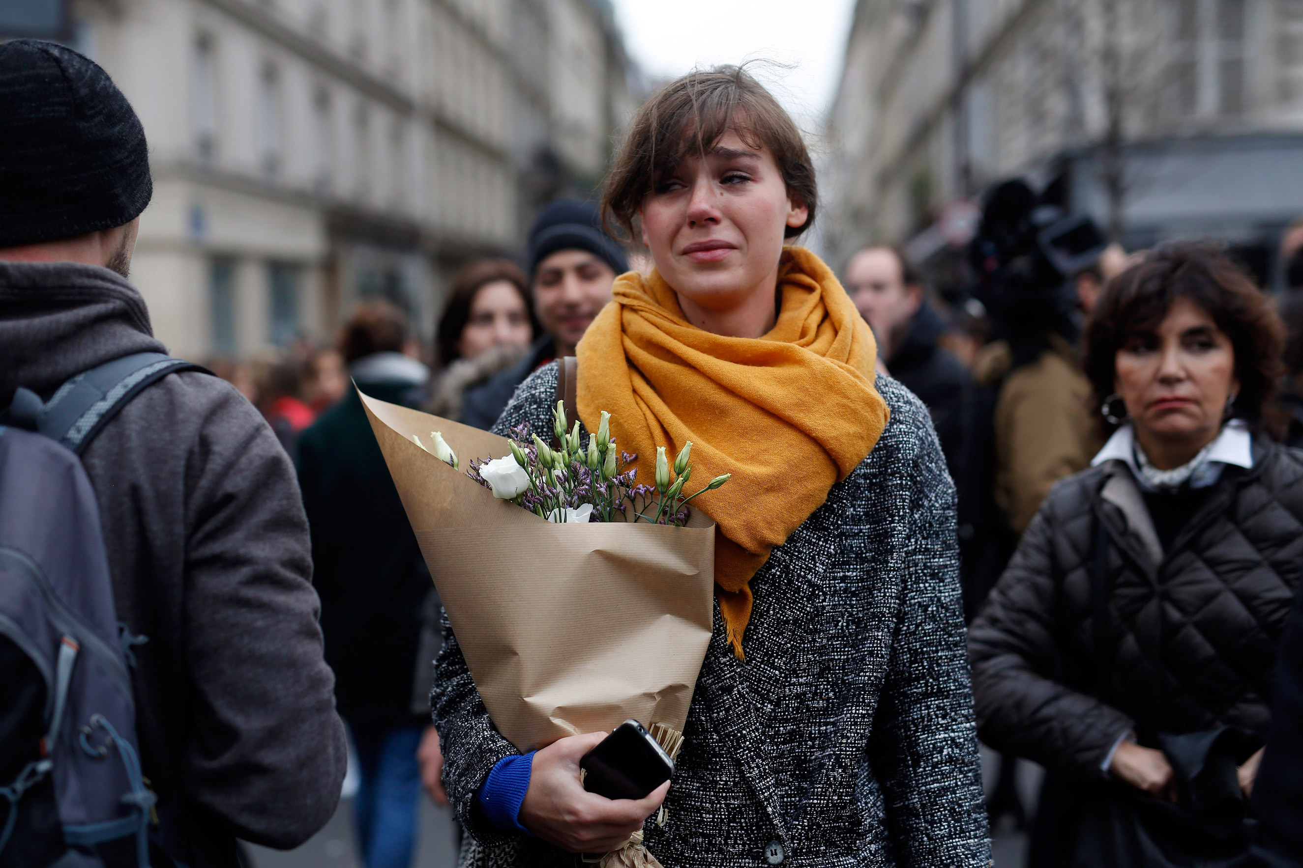 A woman carrying flowers cries in front of the Carillon cafe and the Petit Cambodge restaurant in Paris on Nov. 14, 2015.