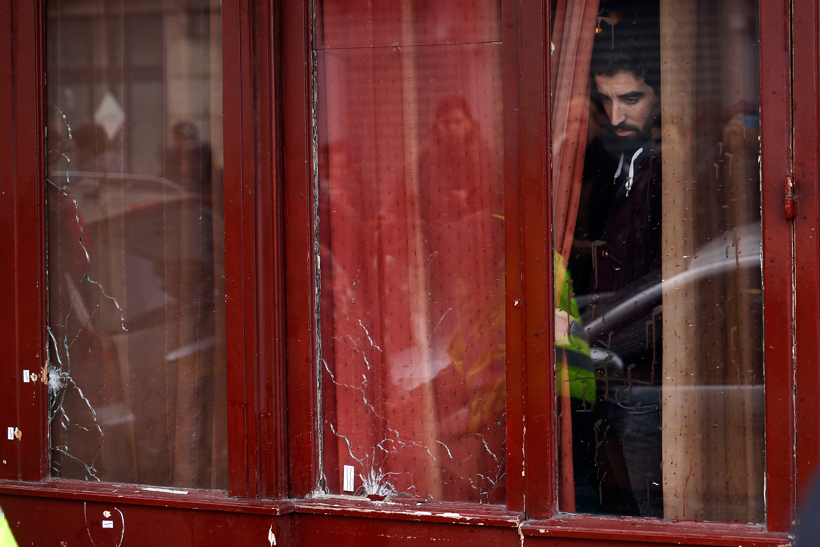 A man looks out the bullet ridden windows of the Carillon cafe in Paris on Nov. 14, 2015.