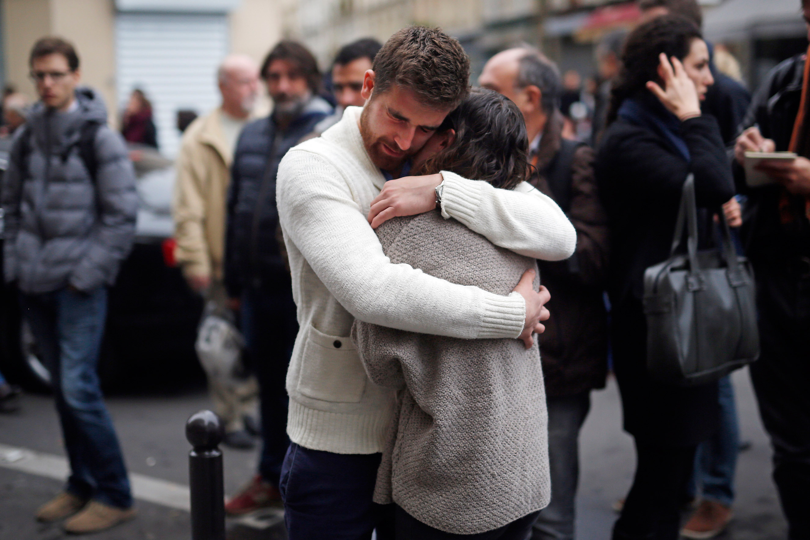 People react in front of   the Carillon cafe and the Petit Cambodge restaurant in Paris on Nov. 14, 2015.