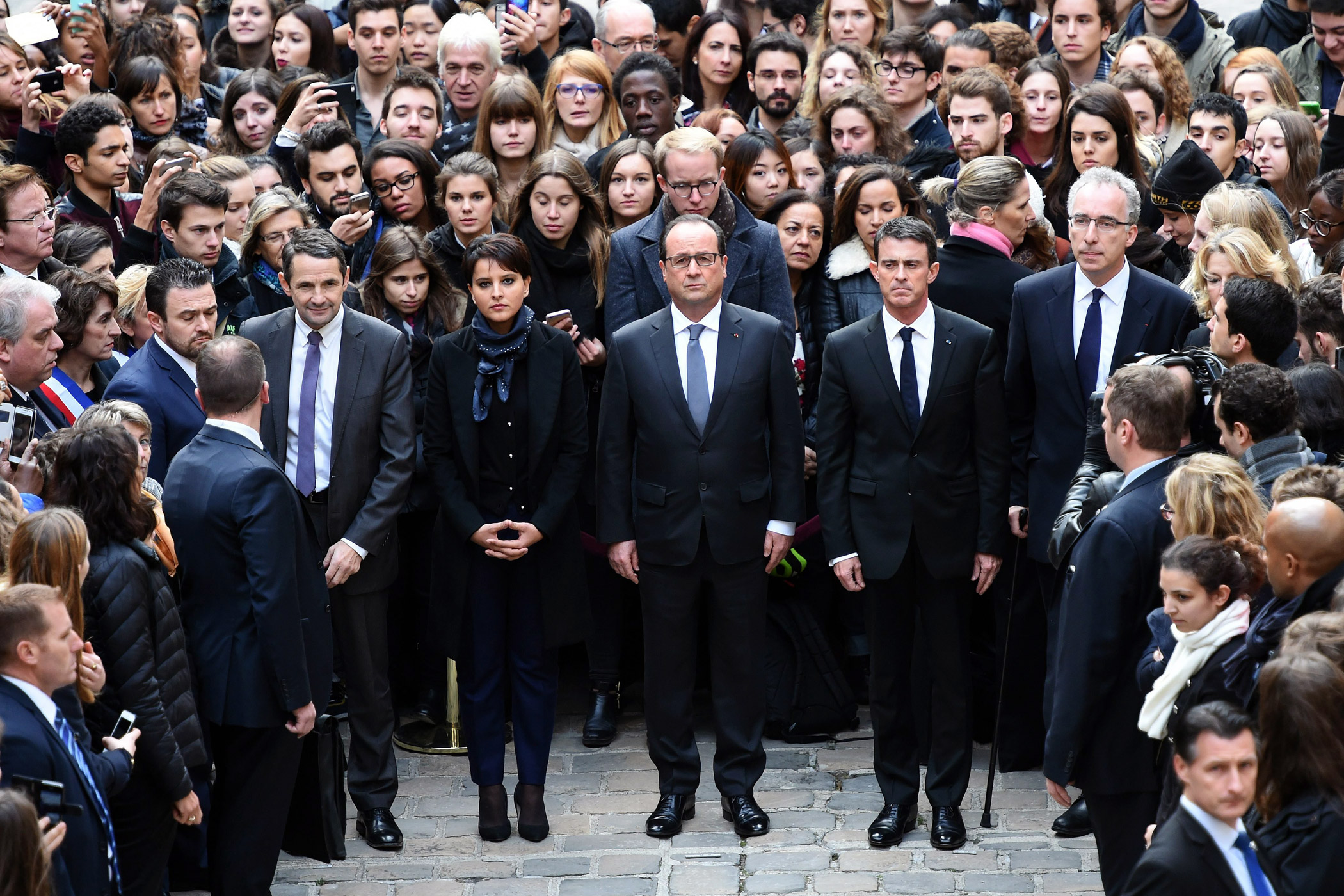 French President Francois Hollande, center, observes a minute of silence for the victims of the Nov. 13 attacks on Paris at the Sorbonne University on Nov. 16, 2015.  French Minister for Higher Education and Research Thierry Mandon, center left, French Education Minister Najat Vallaud-Belkacem, and French Prime Minister Manuel Vallse join Hollande.