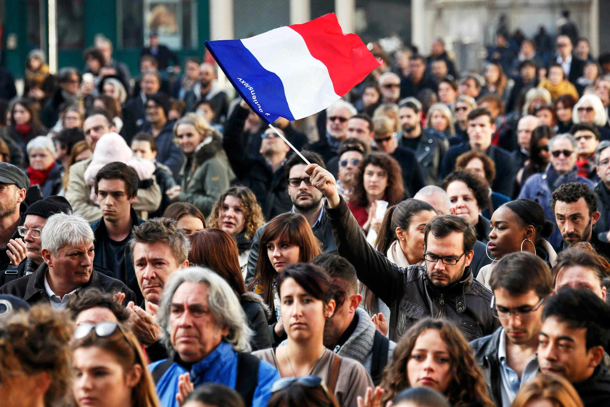 A man waves a French flag during a minute of silence in Lyon, France.