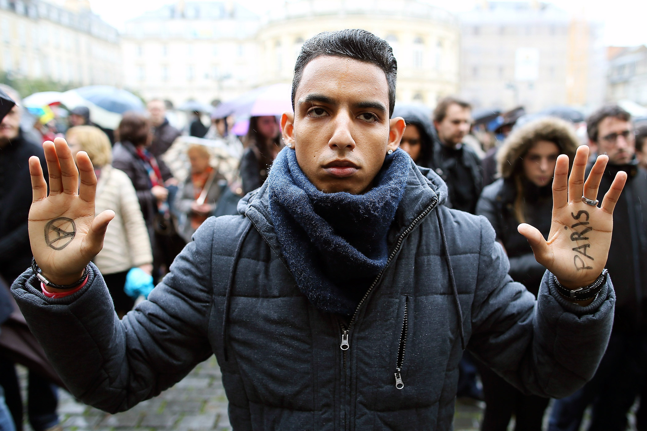 A man holds up his hands during a minute of silence for victims of Paris attacks in Rennes, western France.
