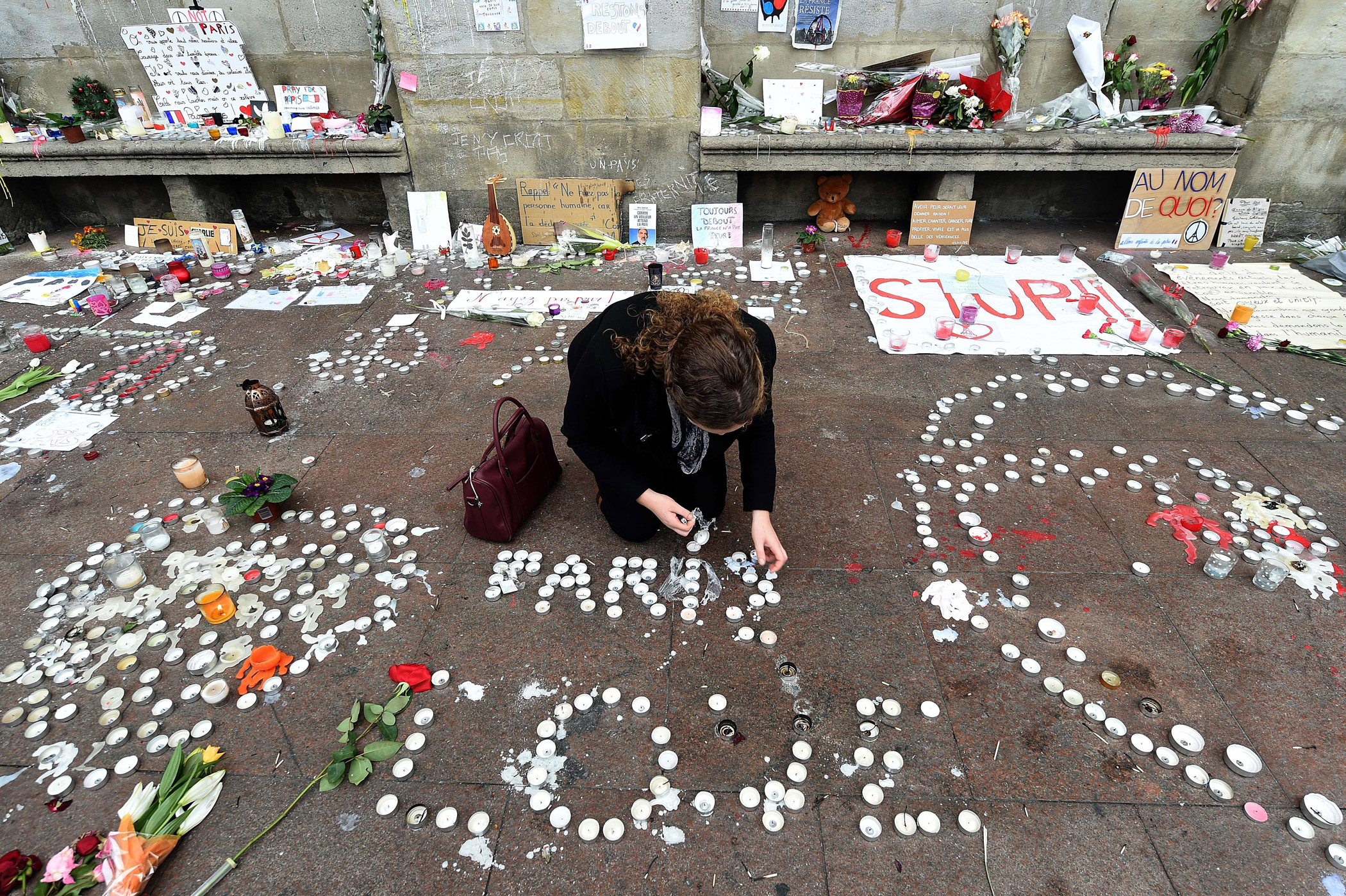 A woman lights candles for a minute of silence on on the Place du Capitole in Toulouse to pay tribute to victims of the attacks in Paris.