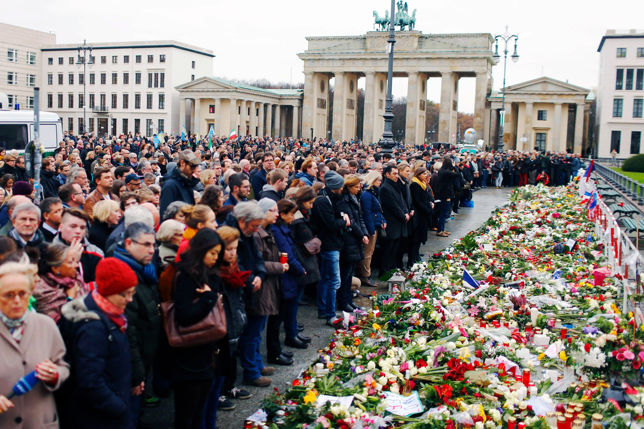 People observe a minute of silence in Berlin near the French embassy to pay tribute to victims of Friday's attacks in Paris.