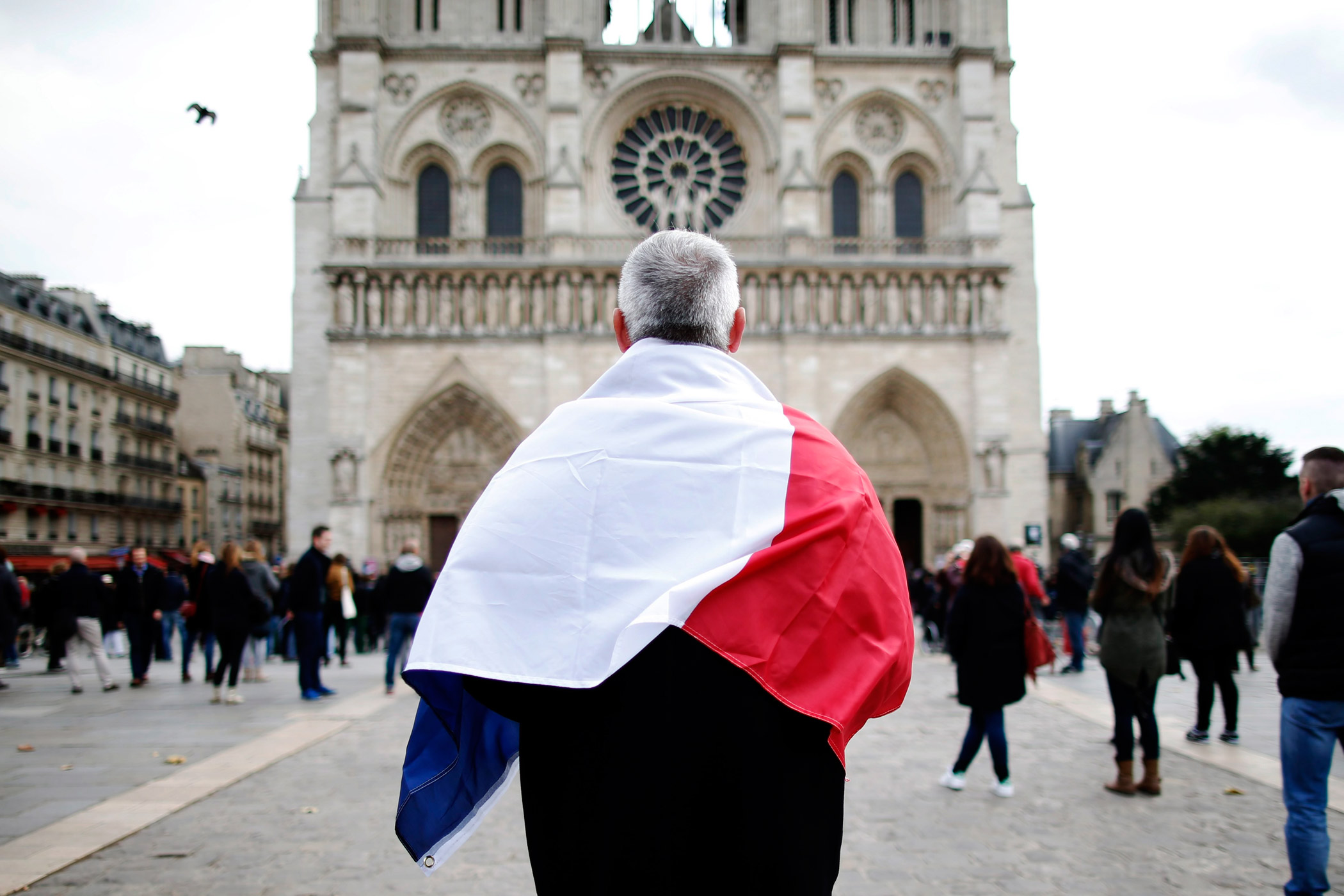 A man observes a minute of silence in front of the Notre Dame Cathedral in Paris.