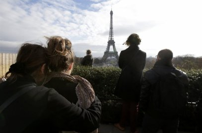 People observe a minute of silence at the Trocadero in front the Eiffel Tower to pay tribute to the victims of the series of deadly attacks on Friday in Paris