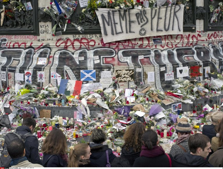 People gather to observe a minute of silence at the Place de la Republique in memory of the victims of terror attacks on Paris.