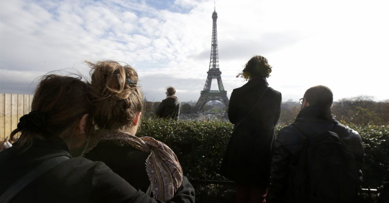 Mourners observe a minute of silence at the Trocadero in front the Eiffel Tower to pay tribute to the victims of the attacks on Paris.