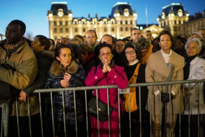PARIS, FRANCE - NOVEMBER 15: People gather outside of Notre Dame cathedral ahead of a ceremony to the victims of friday's terrorist attacks on November 15, 2015 in Paris, France. As France observes three days of national mourning members of the public continue to pay tribute to the victims of Friday's deadly attacks. A special service for the families of the victims and survivors is to be held at Paris's Notre Dame Cathedral later on Sunday. (Photo by David Ramos/Getty Images)