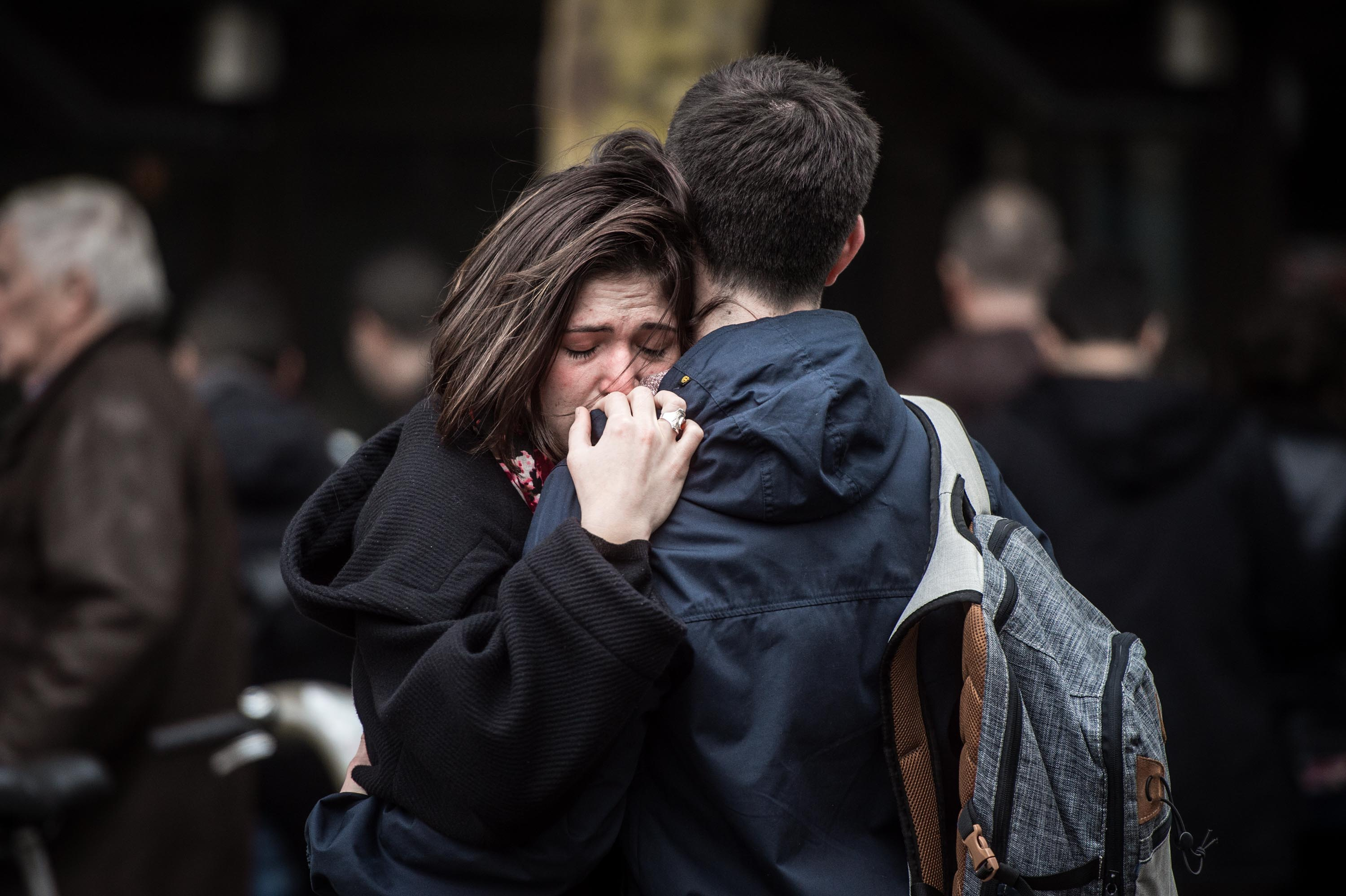 A couple embrace near the Cosa Nostra restaurant in Paris on Nov. 14, 2015.