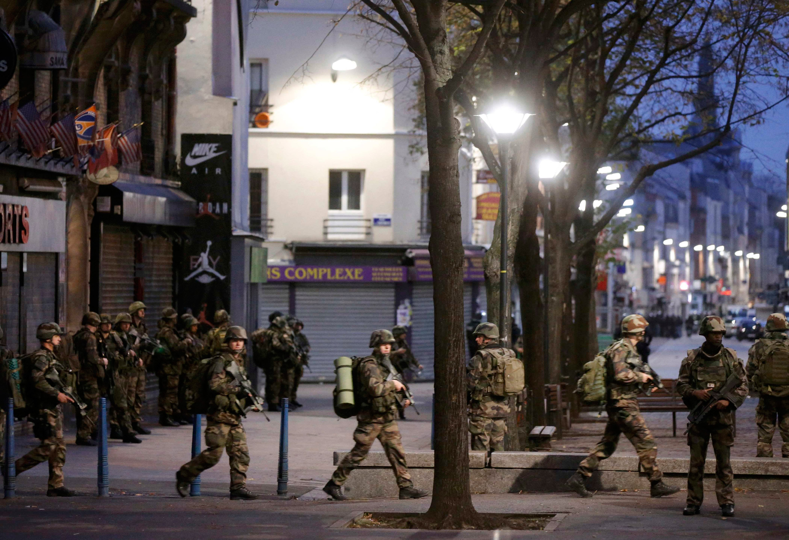 French soldiers secure the area during an operation to catch fugitives from Friday night's deadly attacks in Saint-Denis, outside of Paris, on Nov. 18, 2015.