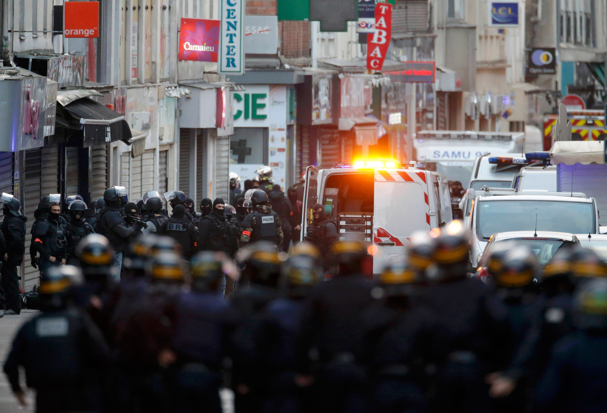 French special police forces secure the area as shots are exchanged during an operation to catch fugitives from Friday night's deadly attacks in Saint-Denis, outside of Paris, on Nov. 18, 2015.