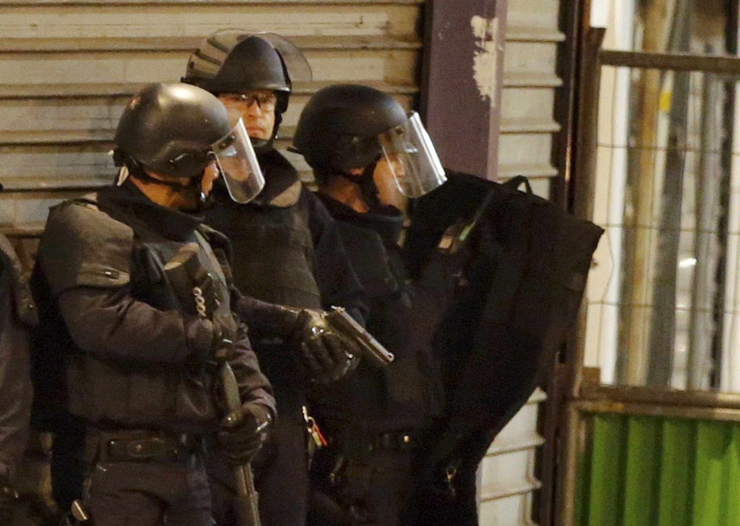 French soldiers secure the area as shots are fired during an operation to catch fugitives from Friday night's deadly attacks in Saint-Denis, outside of Paris, on Nov. 18, 2015.