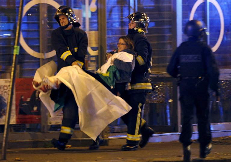 French fire brigade members carry an injured individual near the concert hall following fatal shootings in Paris, on Nov. 13, 2015.