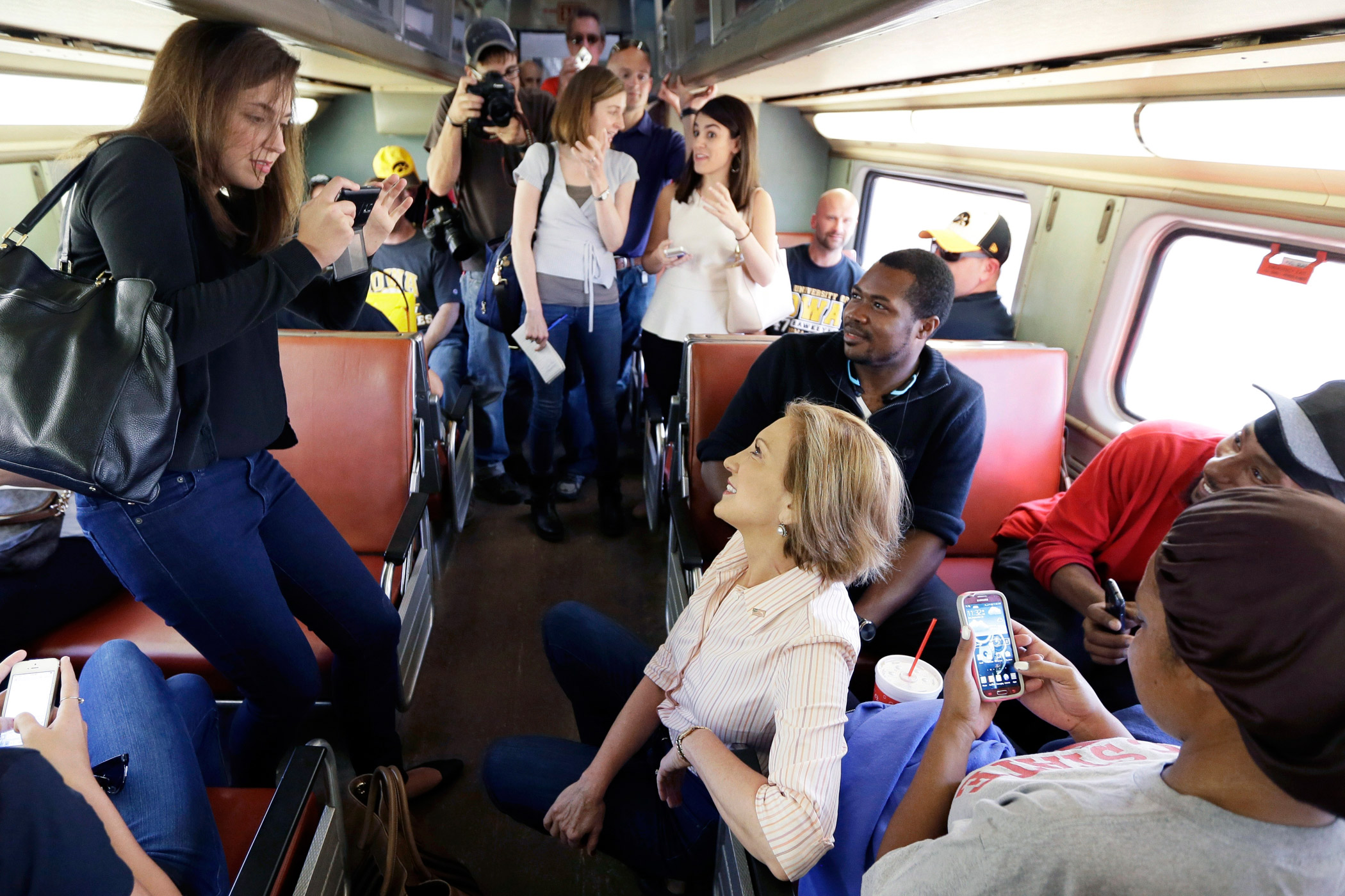 Republican presidential candidate Carly Fiorina, center, rides a train to an event in Iowa City, Iowa on Sept. 26, 2015.
