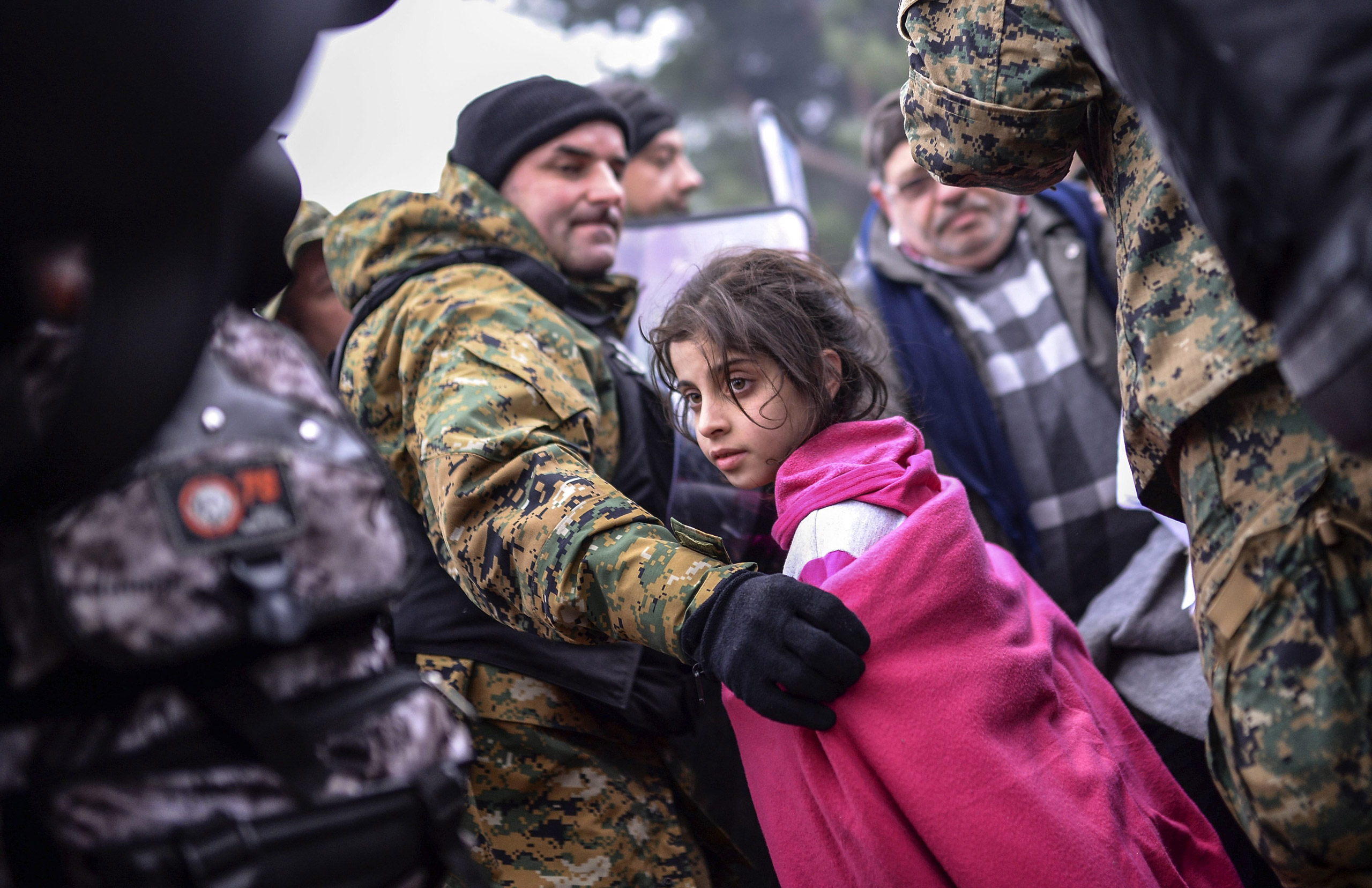 A Macedonian police officer helps a girl move past the cordon on the Greek-Macedonian border after Macedonia has started letting in refugees from Syria, Iraq and Afghanistan, near Gevegelija, Macedonia, on 20 Nov. 2015.