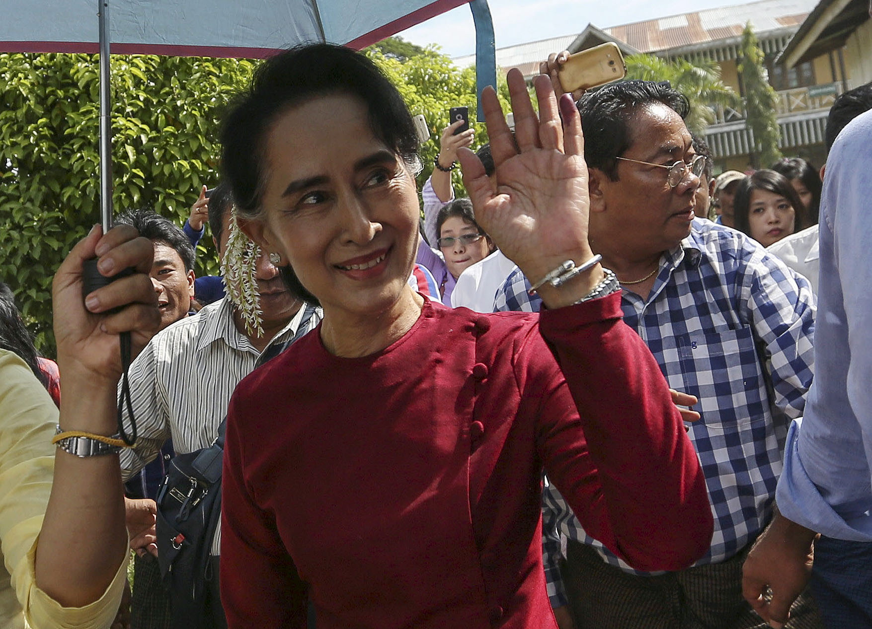 Burmese pro-democracy leader Aung San Suu Kyi waves at supporters as she visits polling stations at her constituency of Kawhmu township on Nov. 8, 2015