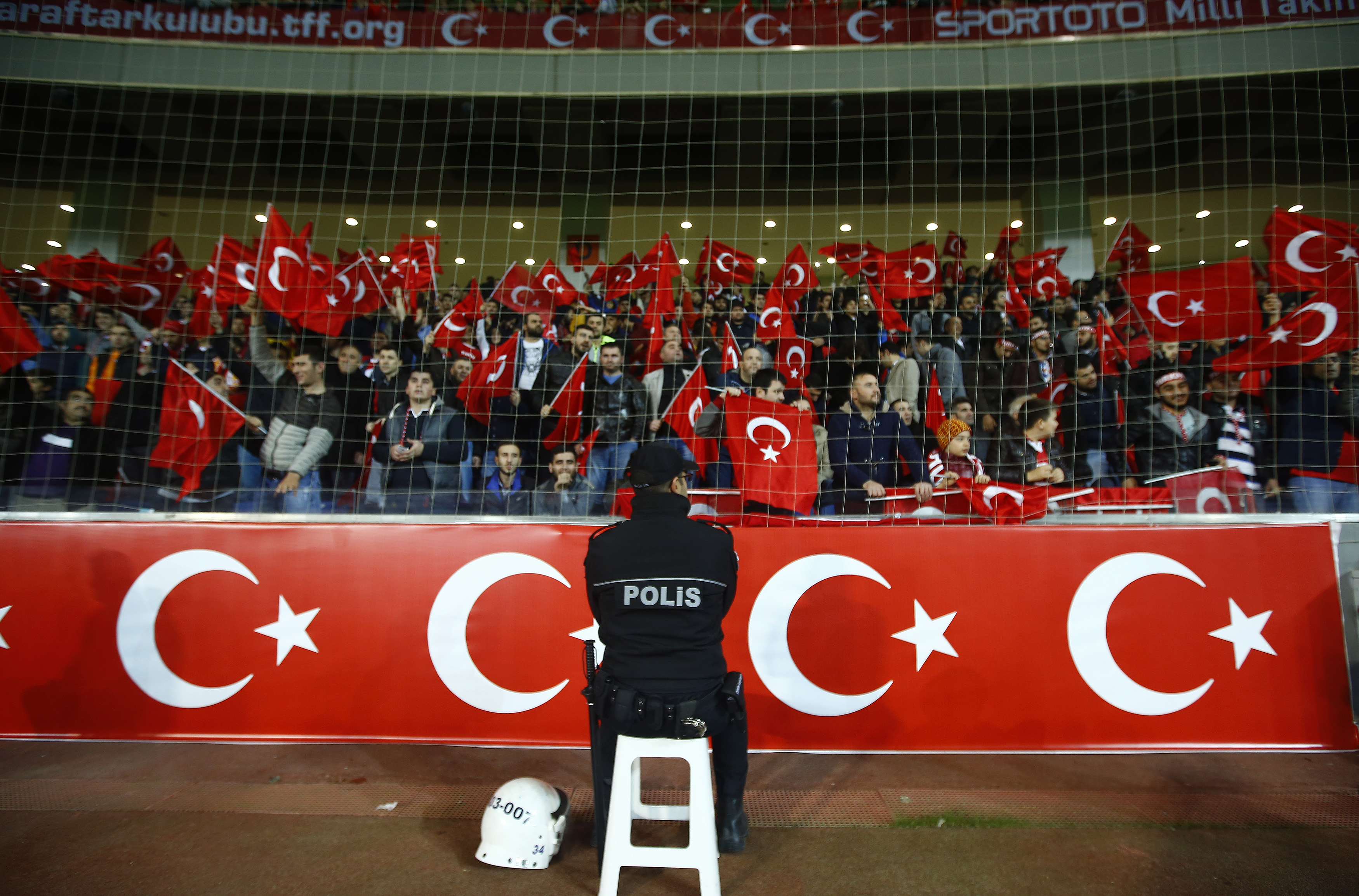 A policeman stands guard in front of supporters of Turkey during their international friendly soccer match against Greece at Basaksehir Fatih Terim Stadium in Istanbul on Nov. 17, 2015
