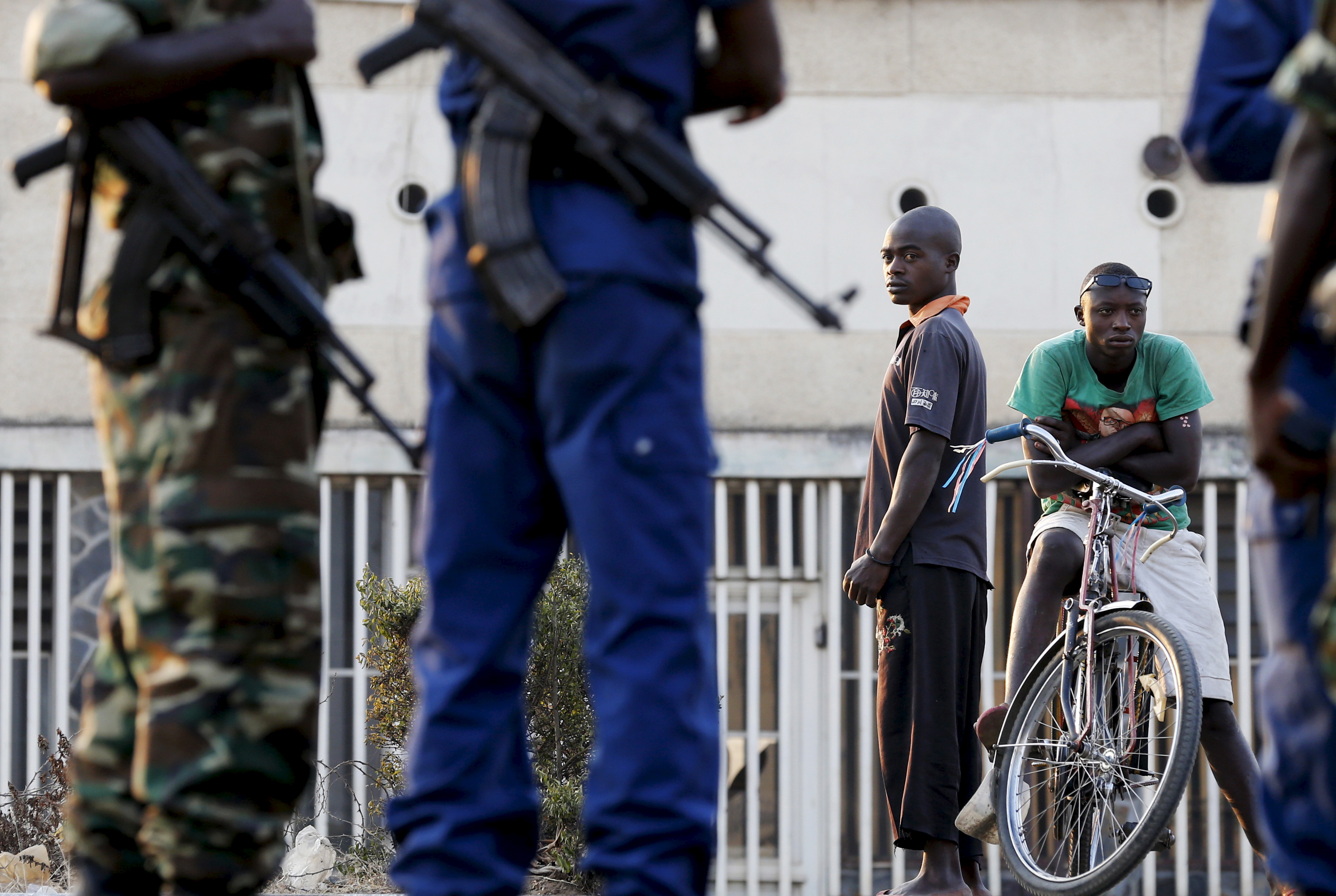 Residents look on as police and soldiers guard a voting station in Burundi's capital Bujumbura during the country's presidential elections, July 21, 2015