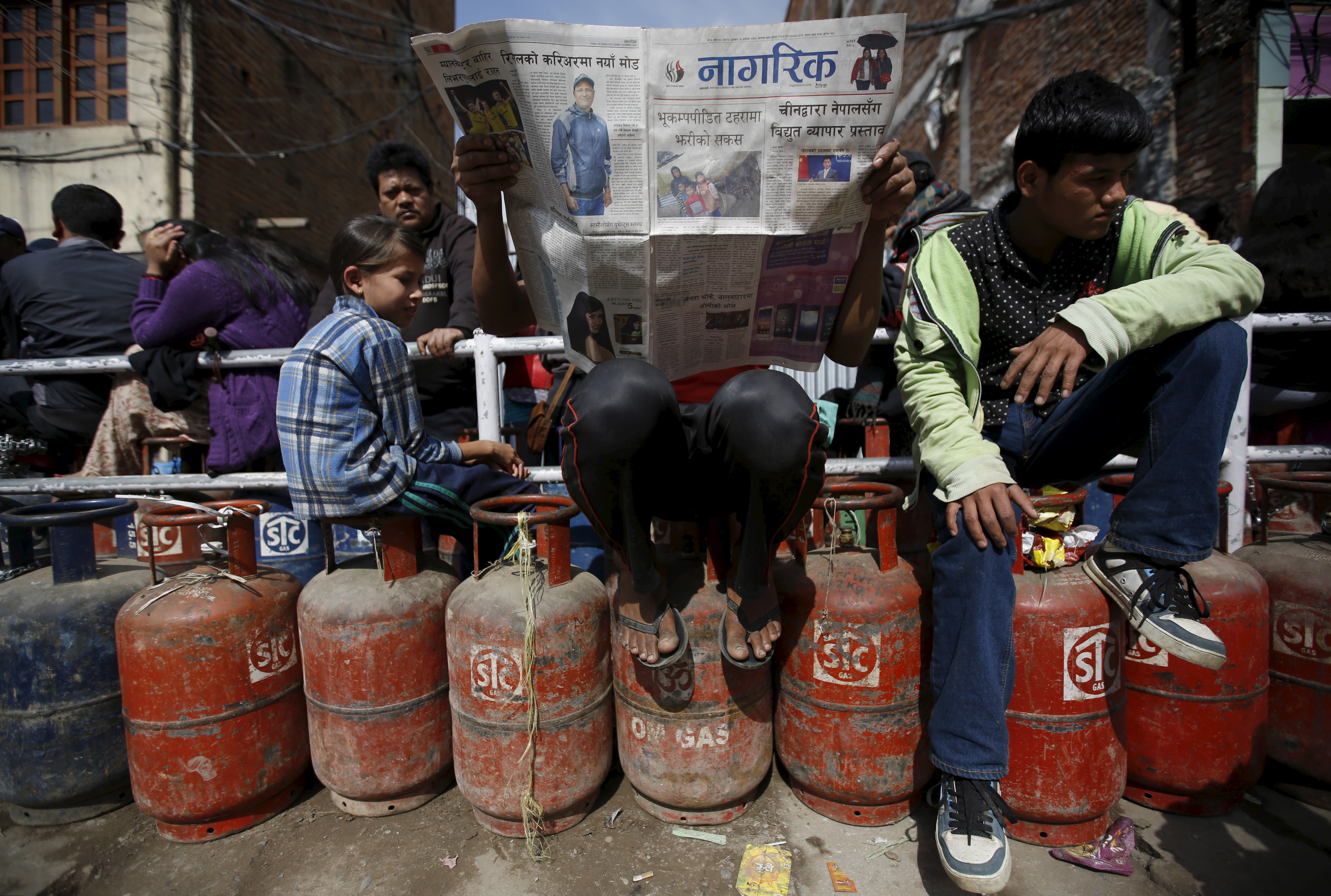 A man, center, reads a newspaper sitting on top of empty cooking-gas cylinder as he waits in a queue to buy cooking gas along with other customers during the ongoing fuel crises that has been continuing for over a month now in Kathmandu on Oct. 30, 2015