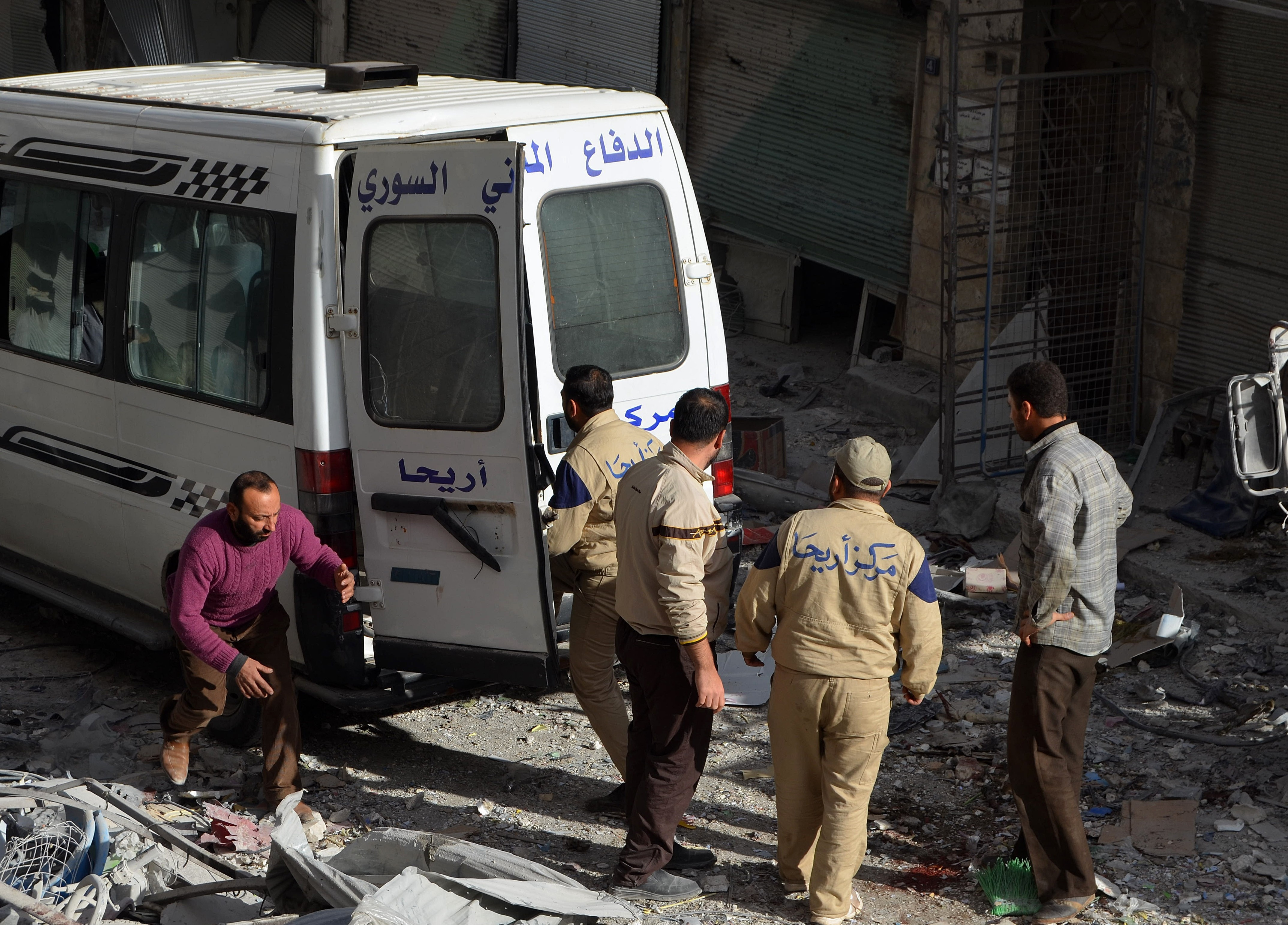 Syrian civil defense members carry a wounded man into an ambulance following the Russian airstrikes targeting a market and residential area in Ariha town Idlib, northern Syria on Nov. 29, 2015.