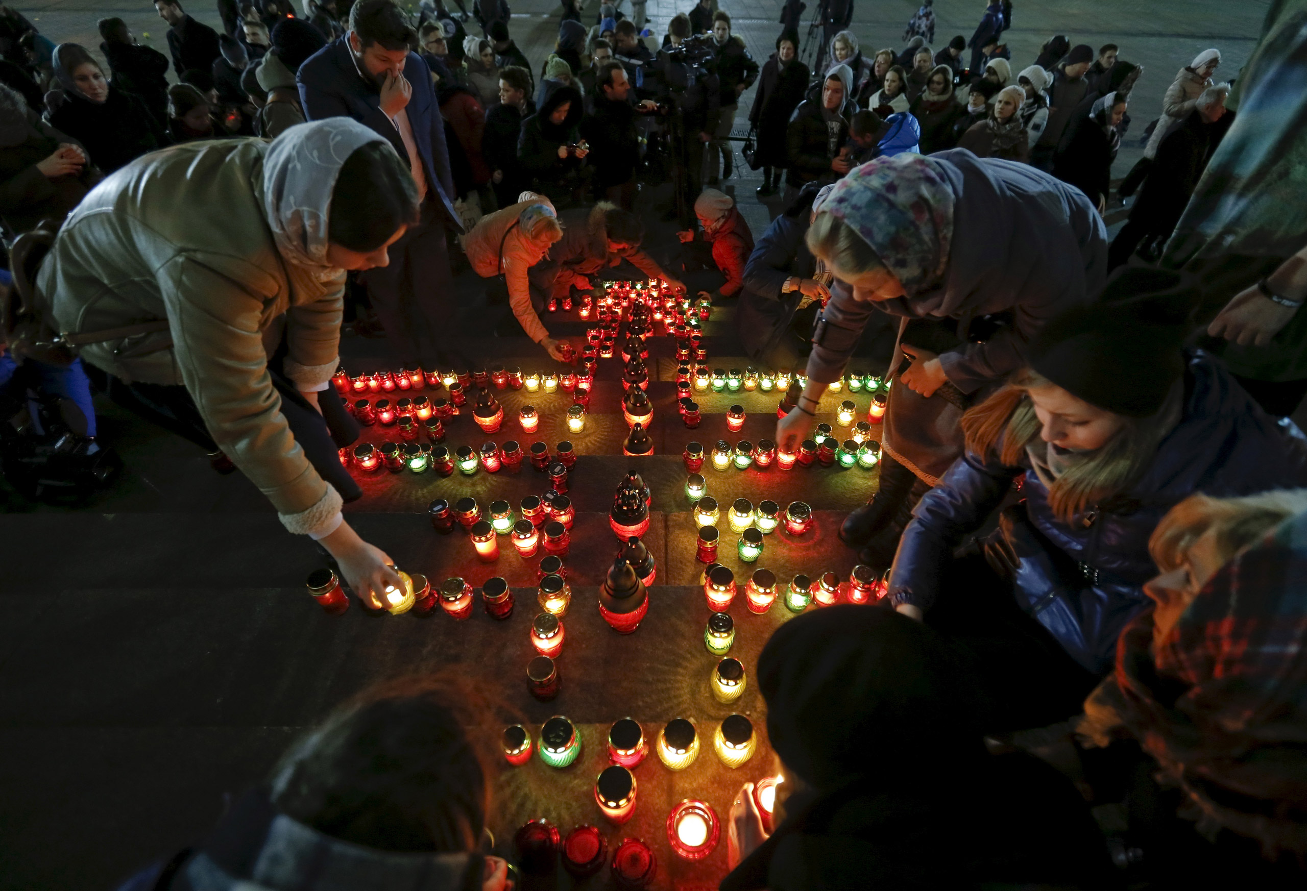 People arrange candles to make a cross to commemorate 224 victims of a Russian airliner which crashed in Egypt, on the stairs of the Christ the Saviour Cathedral in Moscow on Nov. 1, 2015.