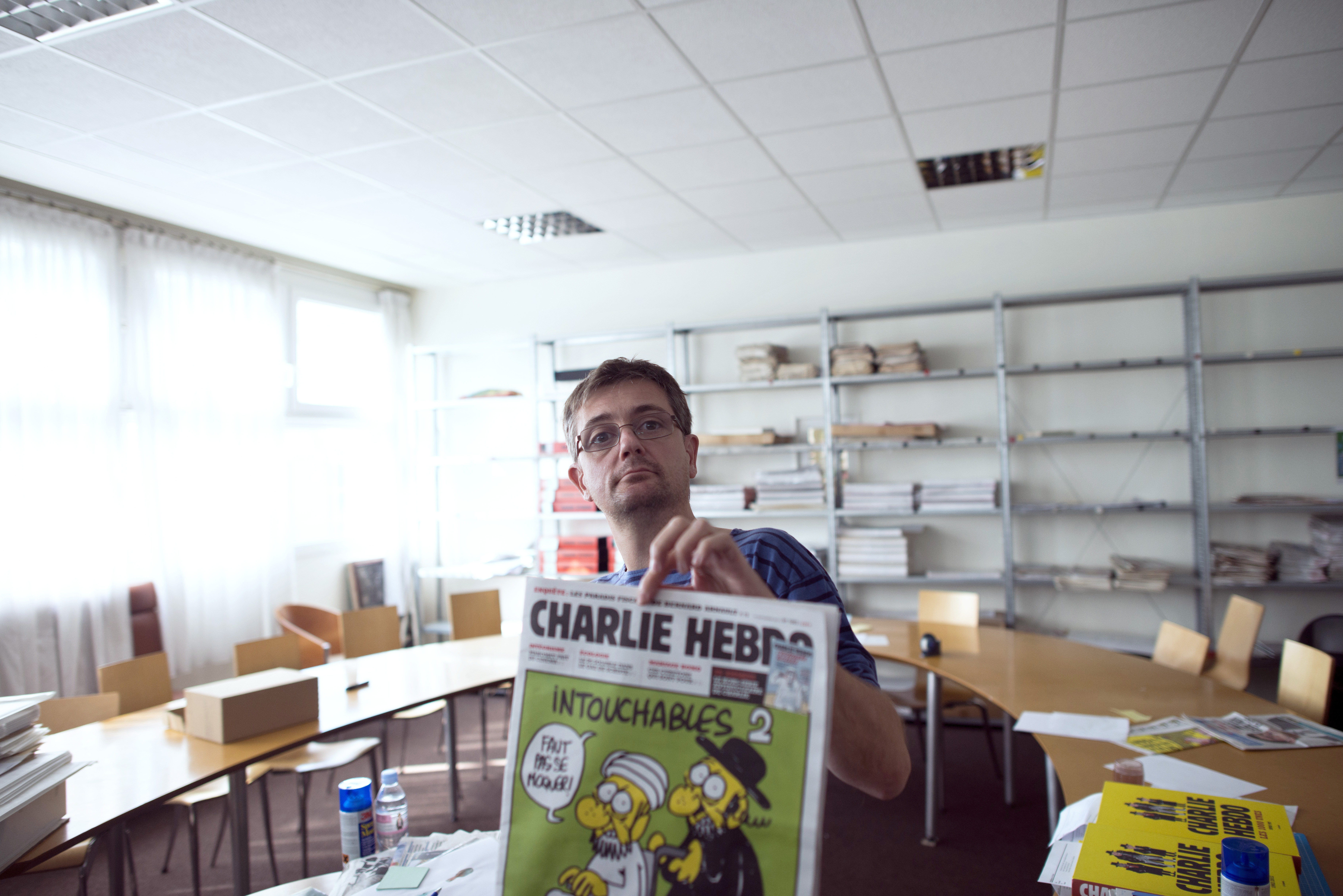 French satirical weekly Charlie Hebdo's publisher and cartoonist presents to journalists the front cover a satirical drawing titled  Intouchables 2  in Paris on Sep. 19, 2012.