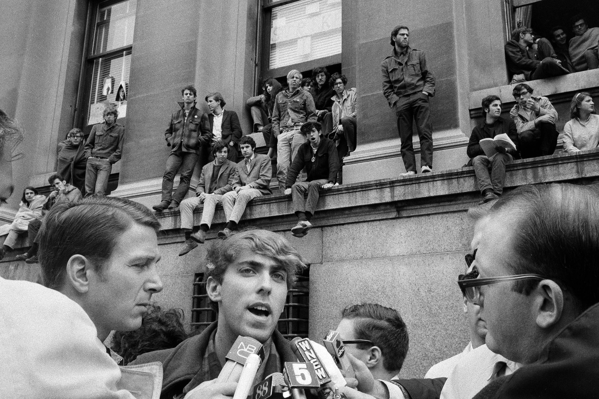 Mark Rudd, a leader of the student protest at Columbia University in New York, speaks to reporters as fellow students, rear, occupy the Low Memorial Library on April 25, 1968. Standing on ledge, center, with hands in pockets, is Juan Gonzalez, another of the student leaders.  The 1968 Columbia University Protests targeted a variety of issues, most notably the Vietnam War. In the aftermath, two of the demands set by students were met: Columbia ended its ties to a controversial weapons-related think tank, and halted a plan to build a disputed gym.