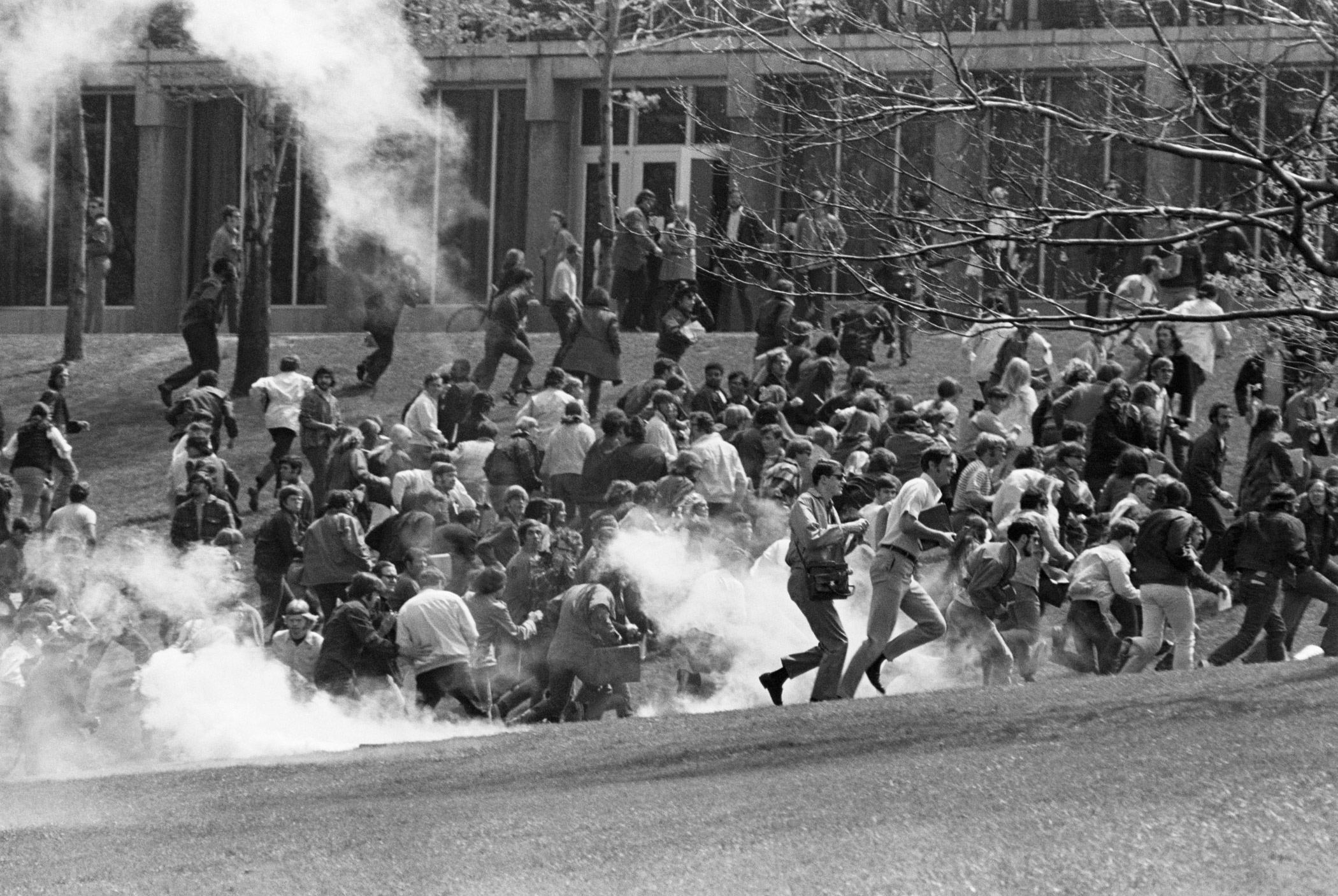 Kent State University students, including anti-war demonstrators, flee as National Guardsmen fire tear gas and bullets into the crowd on May 7, 1970 in Kent, Ohio. The guardsmen killed four students and wounded nine others. The event triggered a national student strike, escalating protests and garnering national media attention for the anti-war movement.